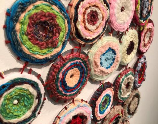 Detail of Woven Together, a wall-mouted series of round shapes woven with yarn