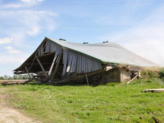 A photograph of a collapsing wood barn in a bright spring landscape of green grass and blue sky