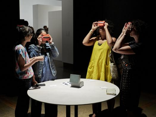 Four women gathered around a round white table in a dark gallery space, looking through slides using Viewmaster toys