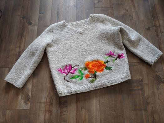 A white knitted sweater spread out on a dark wood laminate floor with a pattern of violet and orange flowers worked into its lower edge