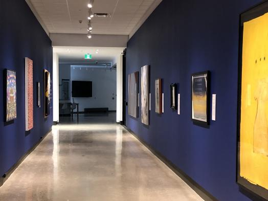 View down the Corridor Gallery towards a darkened lobby, with art on view on two long dark blue walls