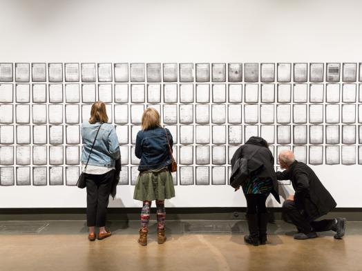 Photo of two pairs of gallery visitors seen from behind as they examine rows of pages of Deanna Bowen's installation of a 1911 petition, which fills the wall to both edges of the photo