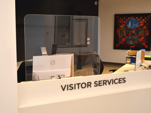 Photo of KWAG Visitor Services desk with plexiglass shield installed