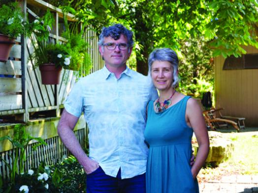 Photo of Trent Bauman and Juanita Metzger, an older couple casually dressed and standing together in a backyard filled with lush greenery