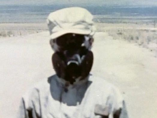 A film still from Trinity 3 shows a close-up view of a figure in light-coloured military fatigues and gas mask against a bleached desert landscape
