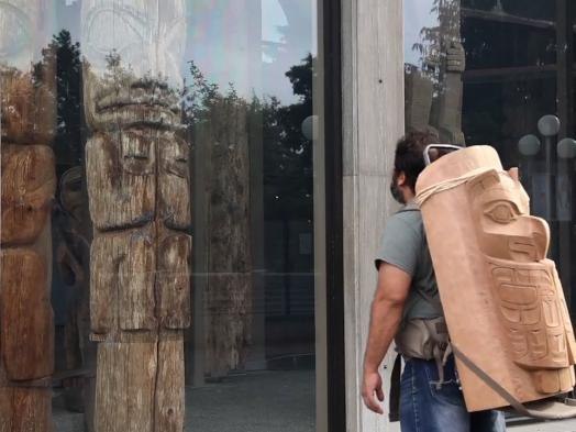 Video still of Luke Parnell's Remediation showing the artist wearing a Haida wood carving on his back, gazing at a totem pole displayed behind glass