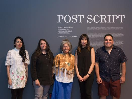 Susan Blight, Lisa Myers, Mary Anne Caibaiosai, Melissa General and Luke Parnell stand together in front of the title wall for Post Script