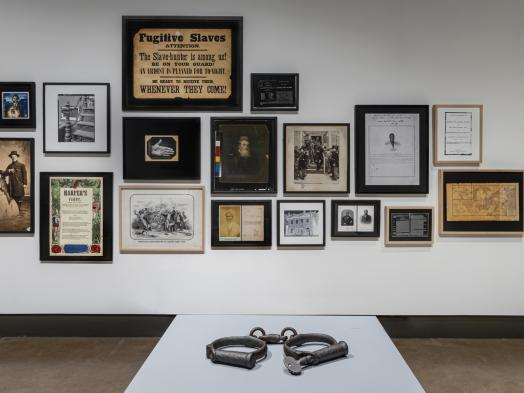 Installation view of Deanna Bowen's Black Drones in the Hive, showing a pair of shackles displayed on a white plinth in front of a wall filled with framed archival images