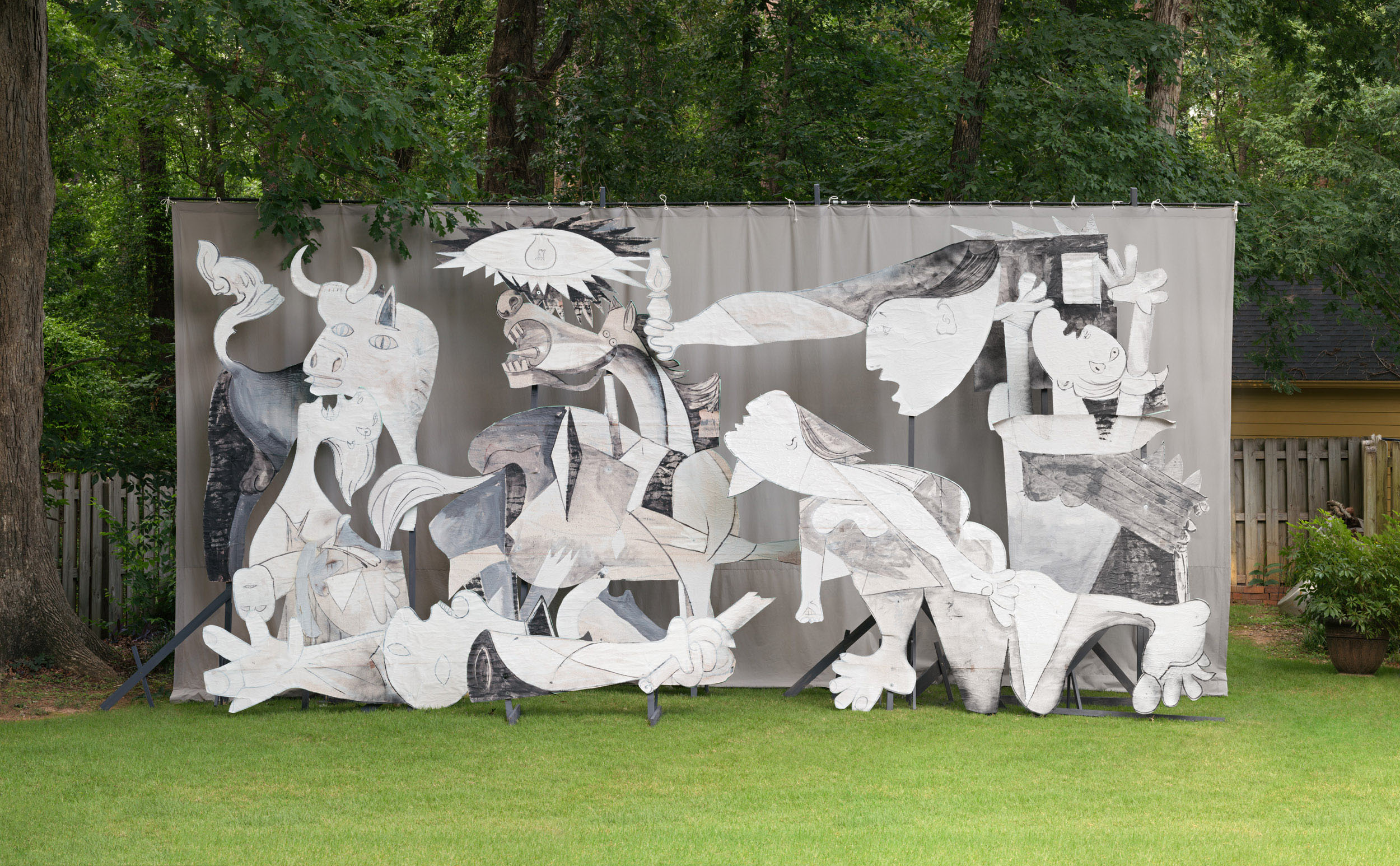 Adad Hannah photo of a restaging of Picasso's Guernica using wood and cardboard cut-outs, arranged in a lush green backyard space