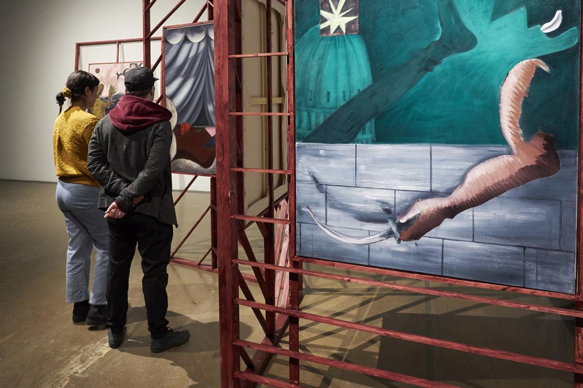 Two gallery visitors looking at geetha thurairajah's paintings displayed in free-standing wooden screens
