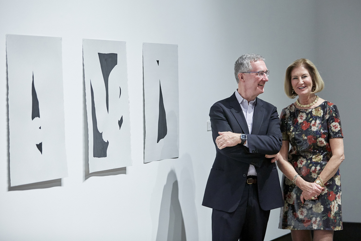 A smiling well-dressed couple pause next to Erika DeFreitas' drawings at a recent tour event
