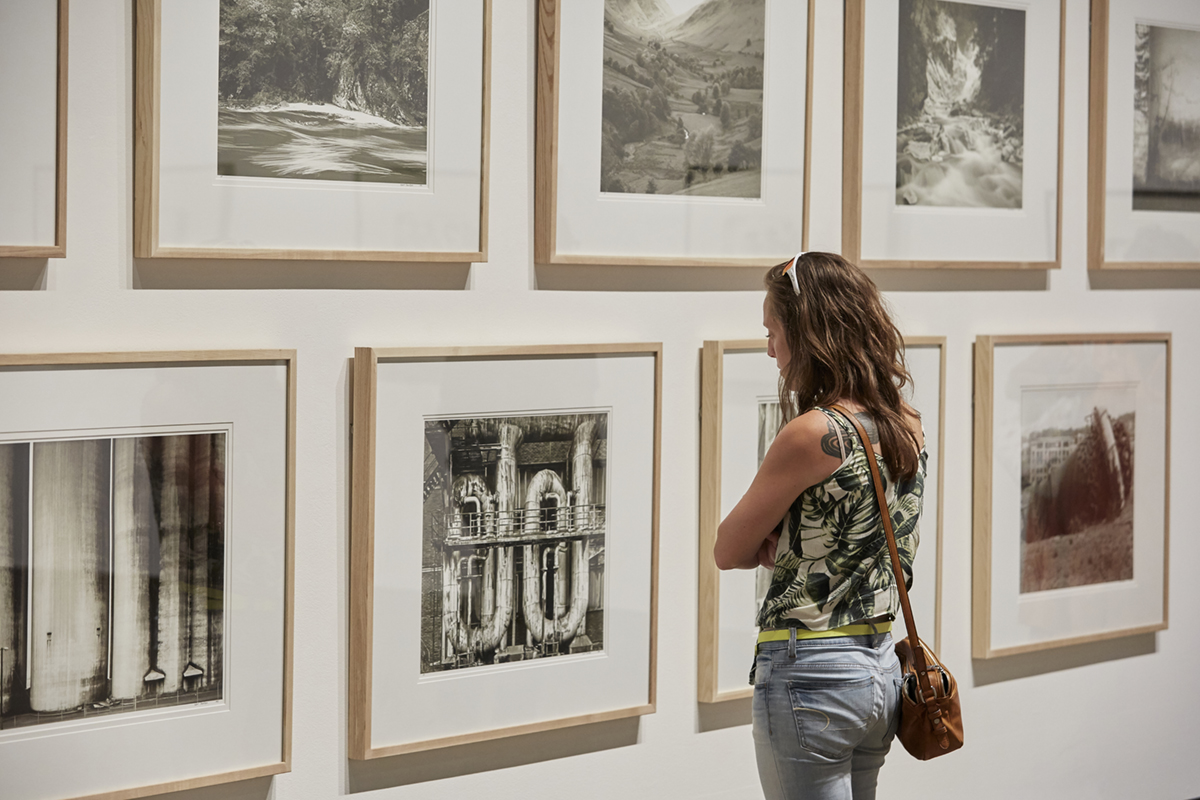 A woman looking at a series of framed Robert Bourdeau photographs in The Perennials