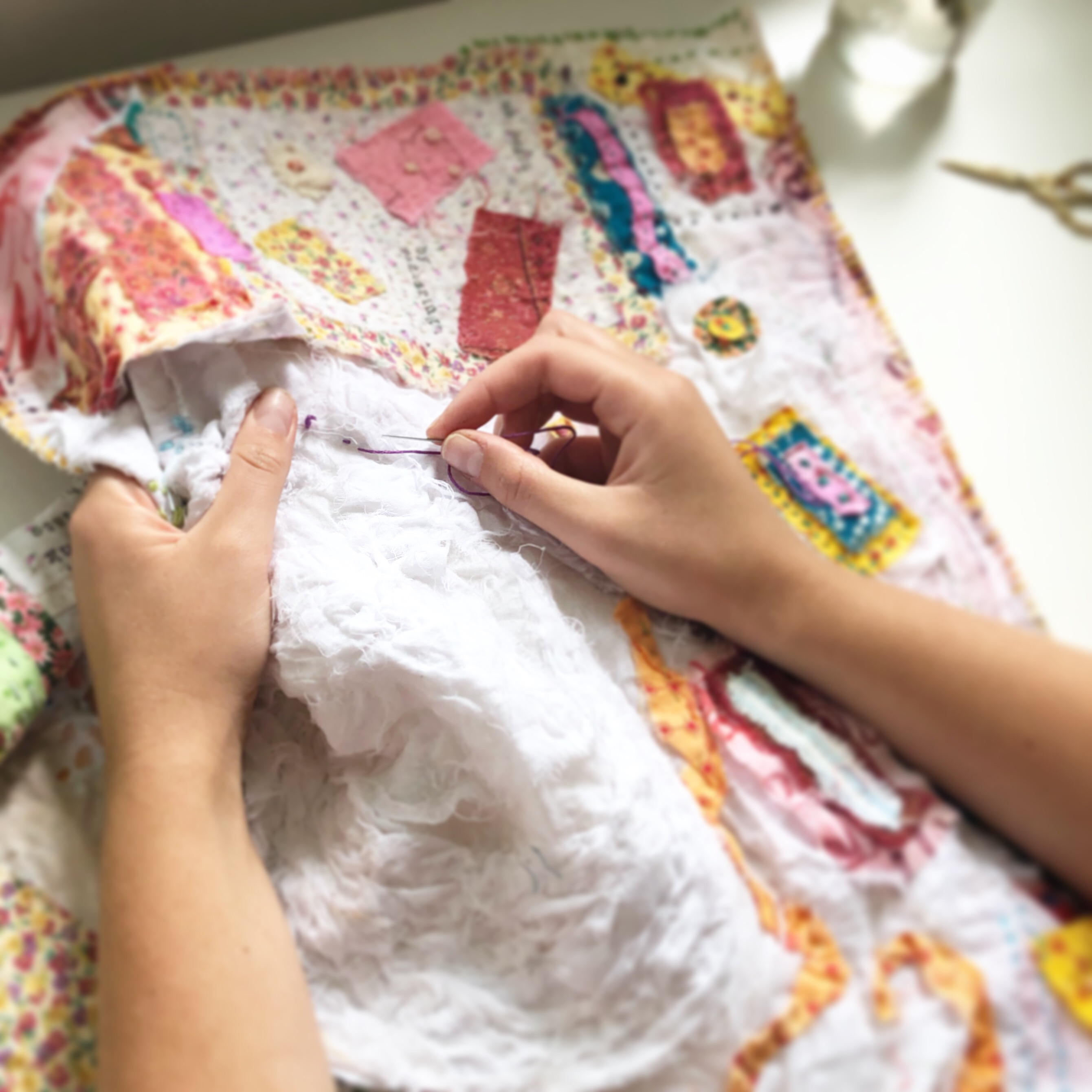 A pair of female hands holding a large piece of white fabric partially covered in pastel-toned embroidery and patches while stitching with dark red thread
