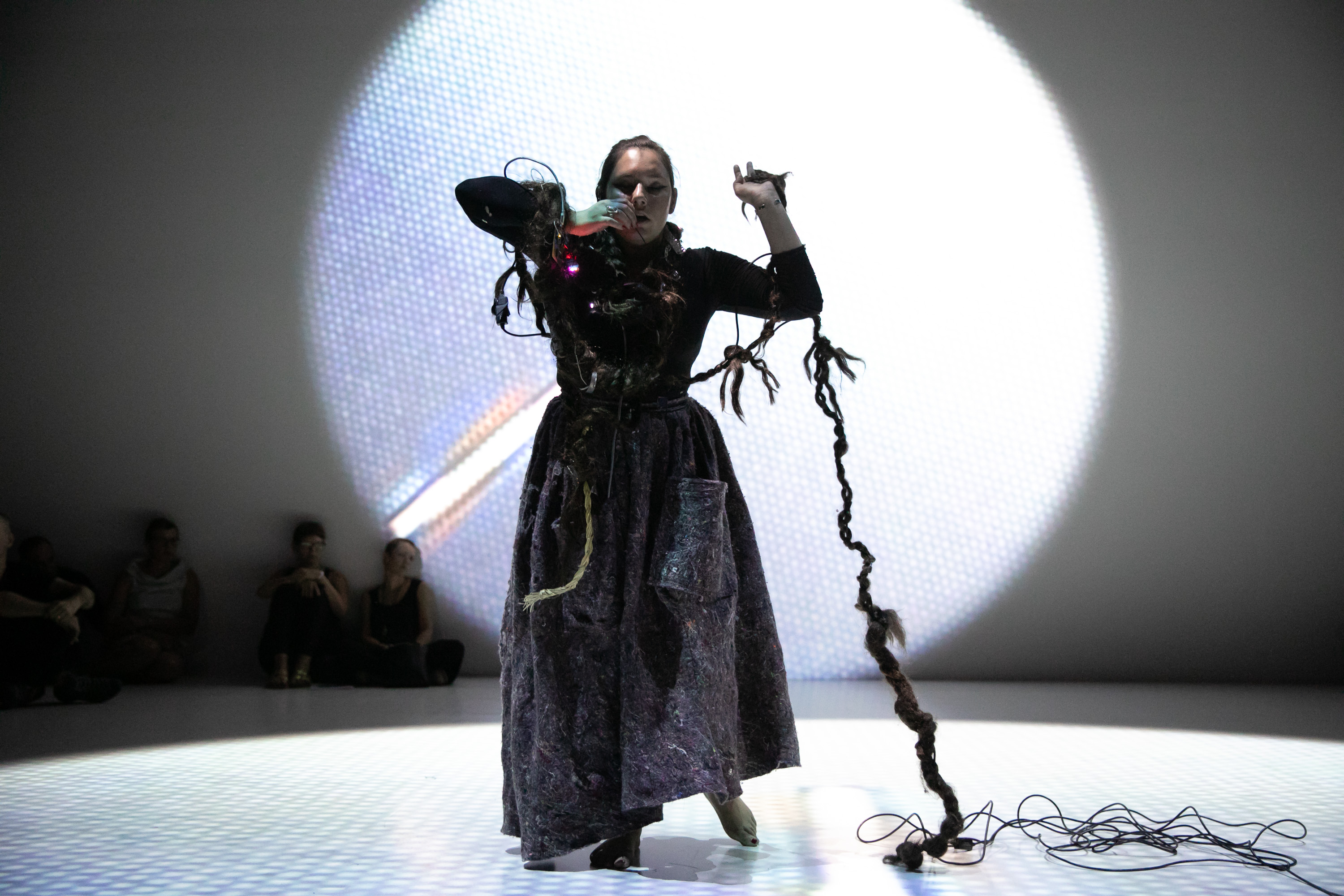 Kite performing in a long dark dress standing on a white-lit circle in a darkened space; a long knotted braid woven with wires extends from her head to the floor