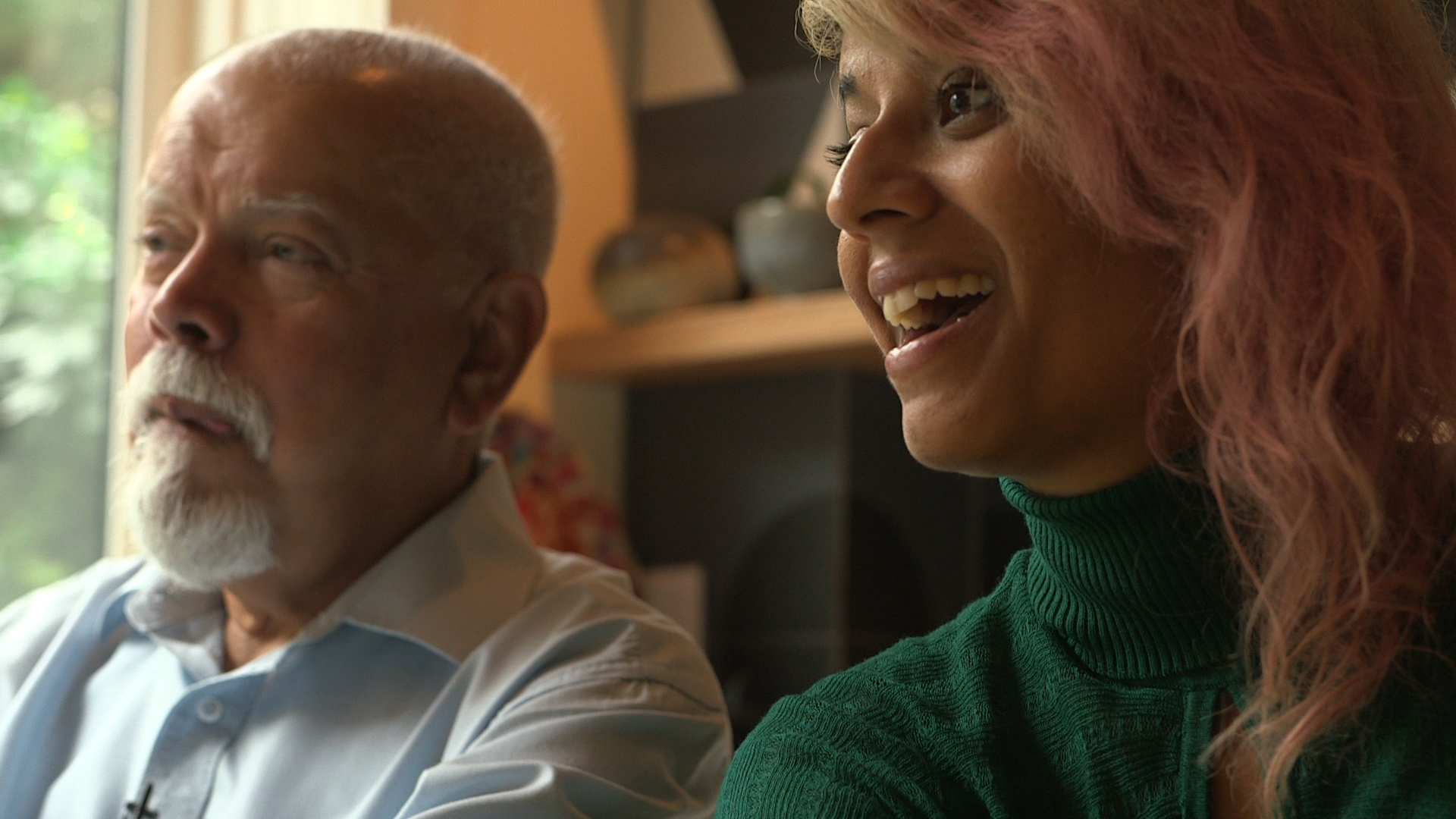A fillm still from Arrival Archives shows a ponderous older man with a white goatee and a younger laughing woman with pink-dyed hair in a warm domestic interior space
