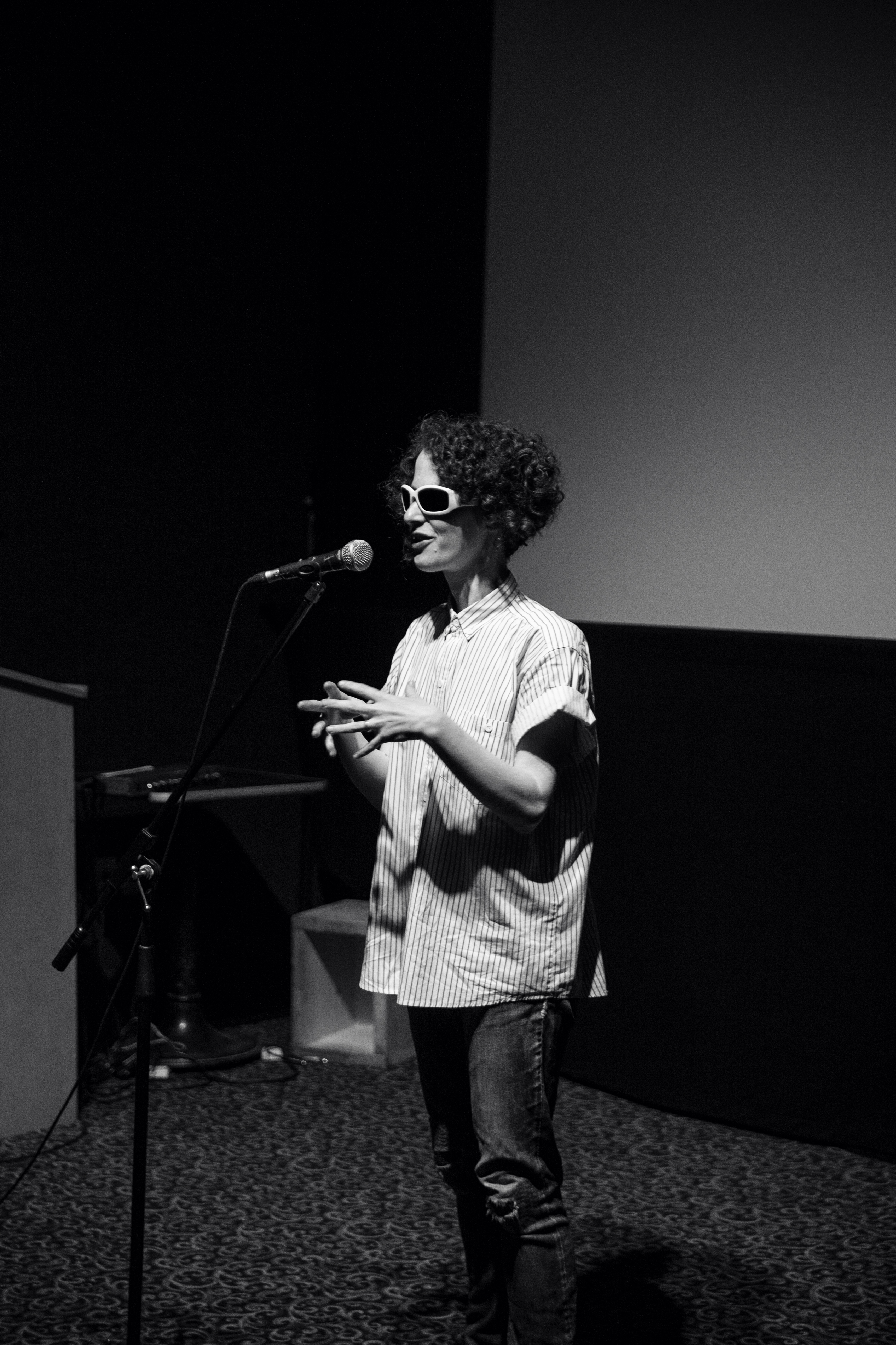 Black and white photo of Aislinn Thomas, a woman with short curly dark hair wearing sunglasses, a loose striped shirt and jeans while speaking at a microphone