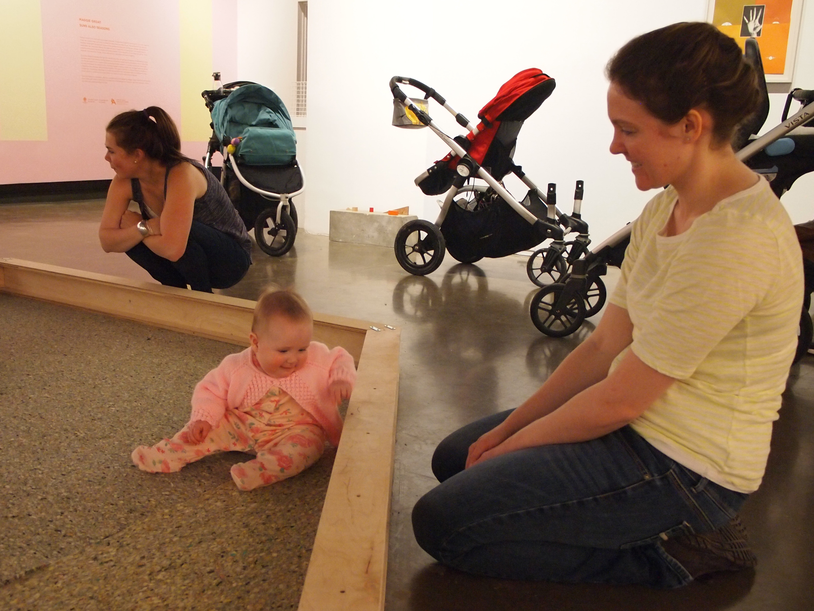 A mother kneels on the floor alongside her infant daughter as she plays inside a Maggie Groat installation on a recent Stroller Tour