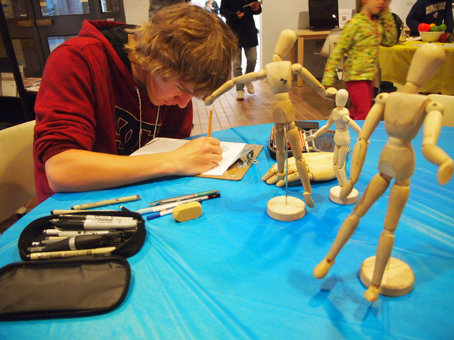 A teenage boy in a red hoodie seated at a table drawing intently from a series of wood mannekin figures