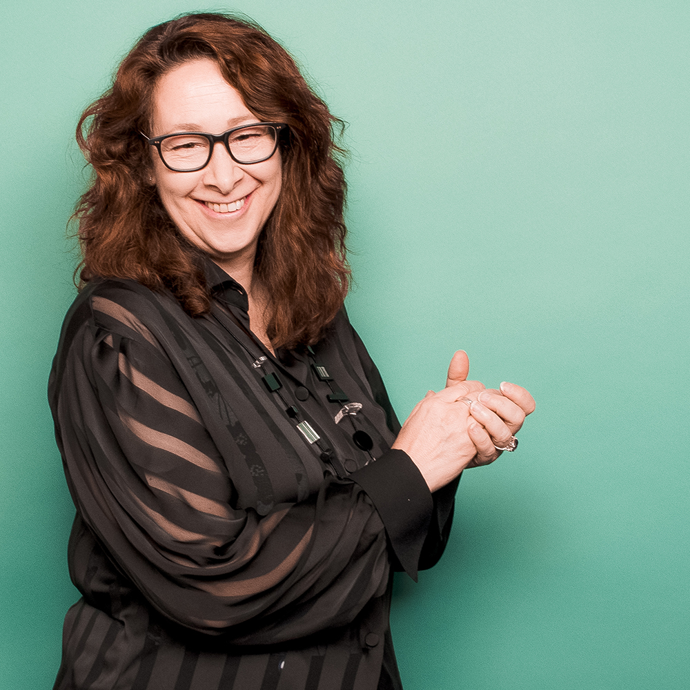 Photo of Caroline Robbie, a smiling middle-aged woman with light brown hair and glasses, posing against a mint green background