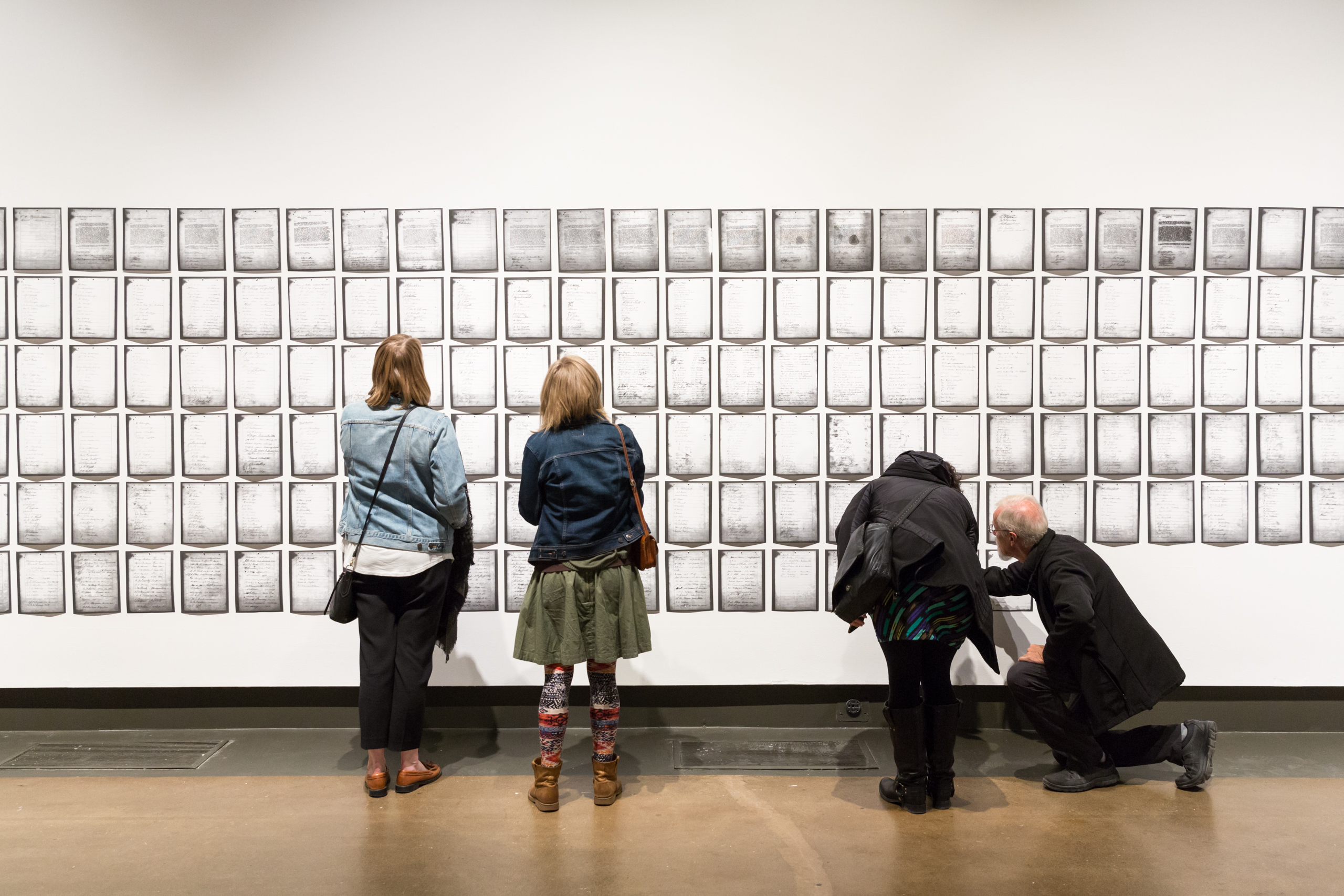 Two pairs of gallery visitors examine different portions of Deanna Bowen's 1911 Anti Creek Negro petition of over 200 pages across a wide white wall