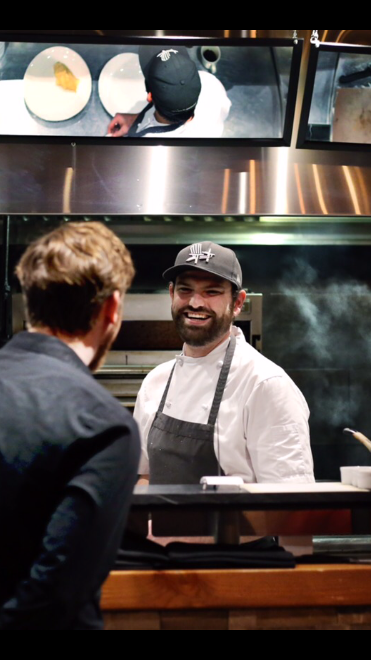 Photo of Chef Kyle Rennie, a young man laughing at the pass in a busy kitchen