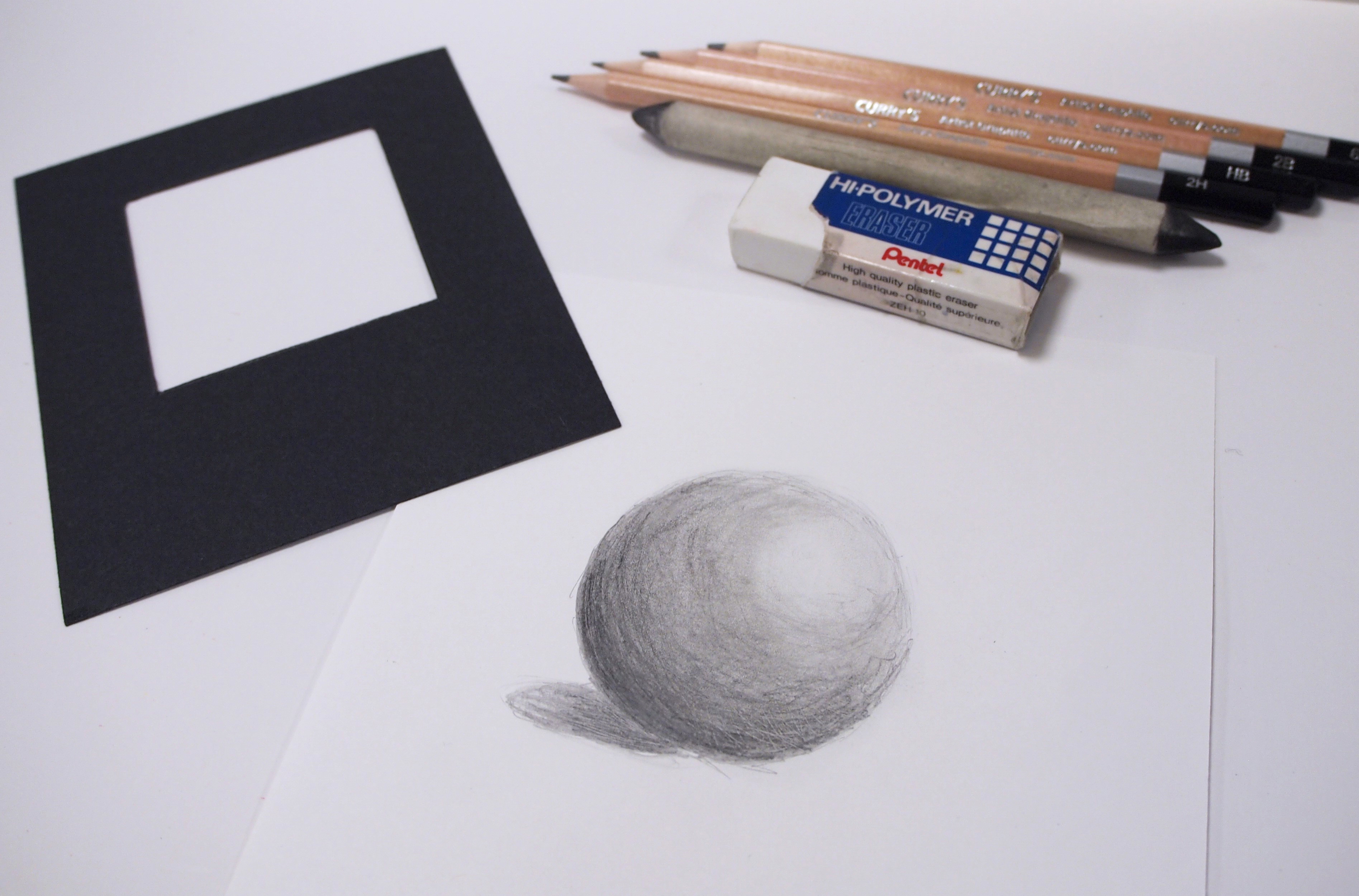 Photo of pencils, eraser, blending stomp and black viewfinder laying alongside a shaded drawing of a sphere