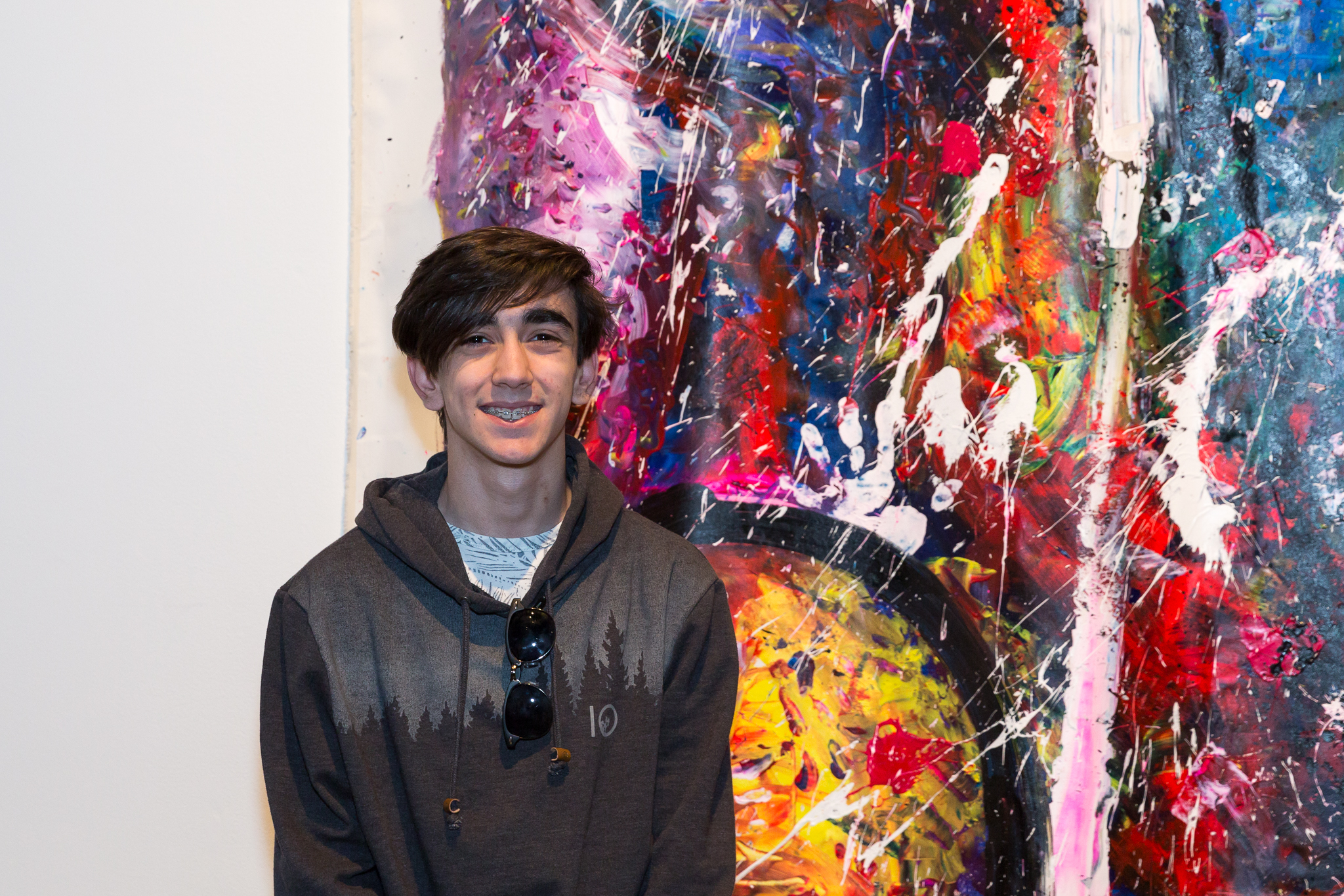 A teenage boy stands smiling in front of a large-scale abstract painting hanging in a white-walled gallery
