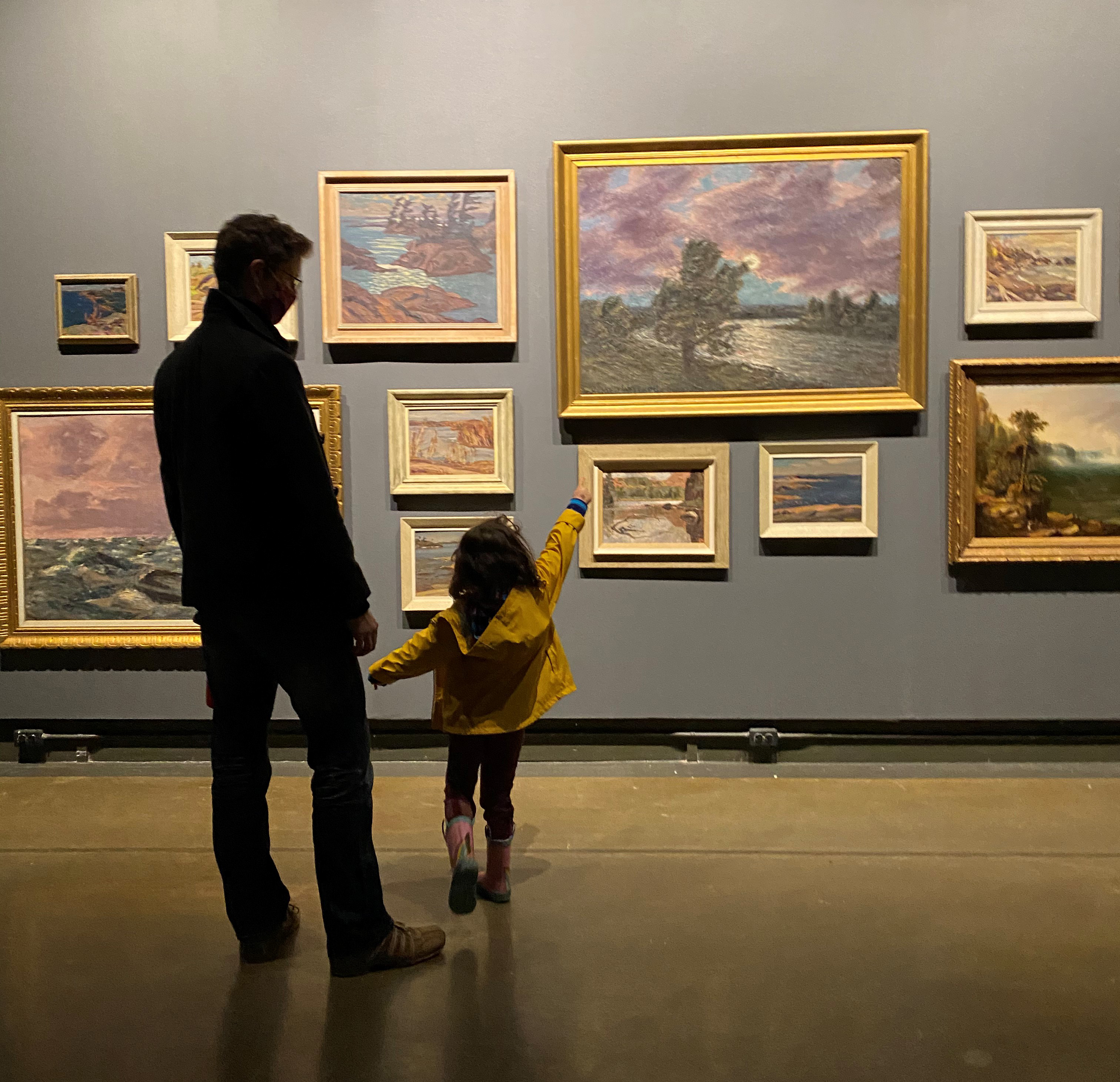 A man accompanies a small child in a raincoat and boots who points excitedly at a dark gallery wall filled salon-style with Canadian landcape paintings of various sizes
