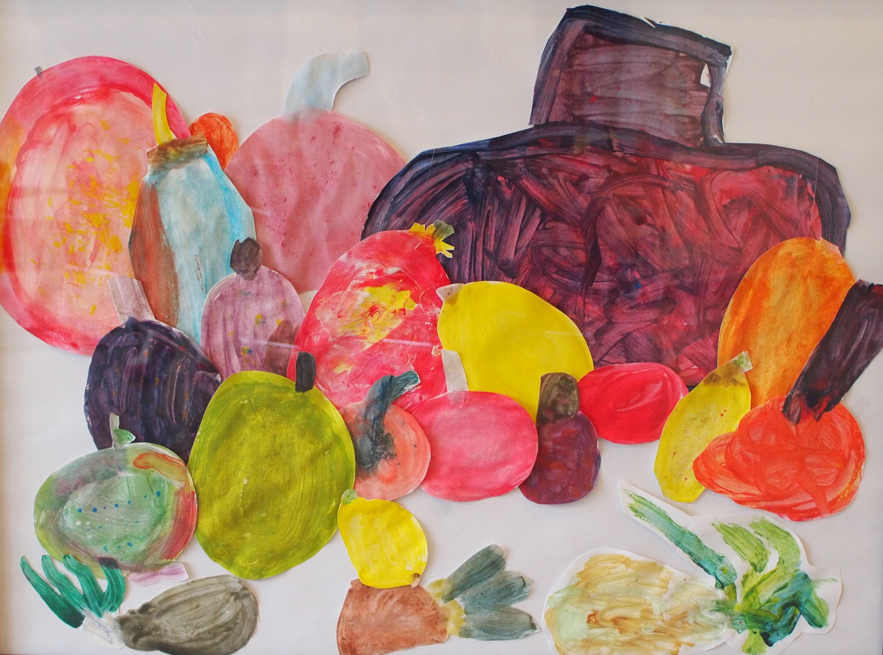 Fruit Bowl, a collaborative collage by Grades 1-2 students featuring cut-out shapes of painted fruit assembled together on a white background