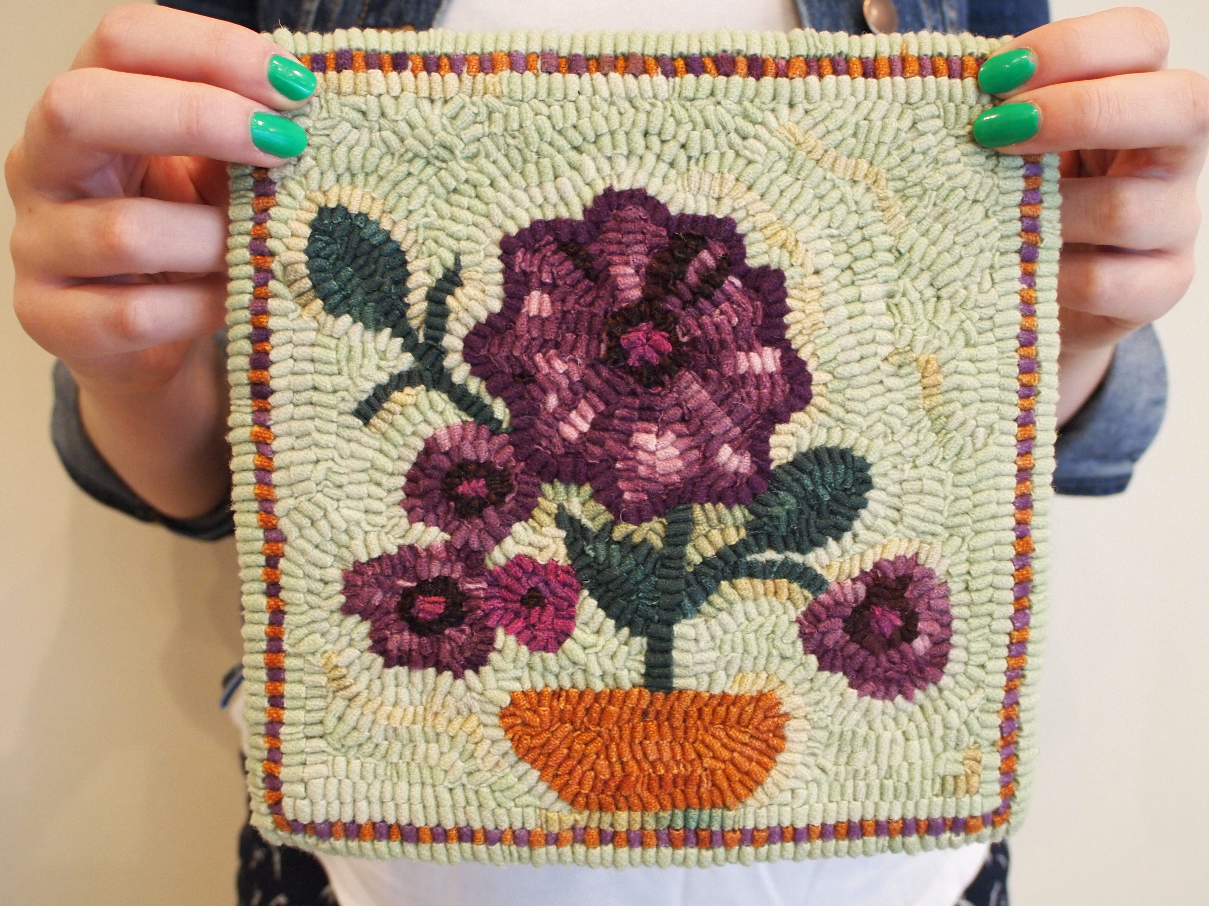 A pair of hands with bright green fingernails holds up a rug hooking piece depicting purple flowers with a light-coloured background