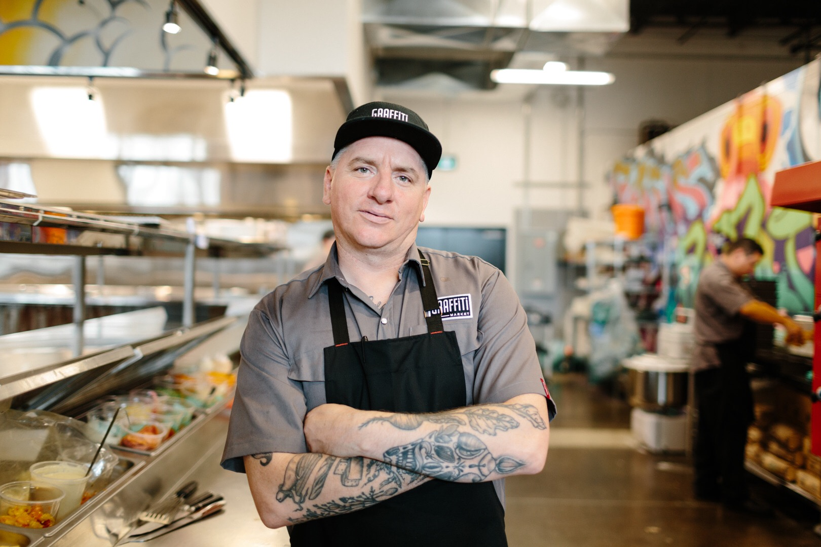 Photo of Chef Brian McCourt standing with tattooed arms crossed in the middle of a large restaurant kitchen