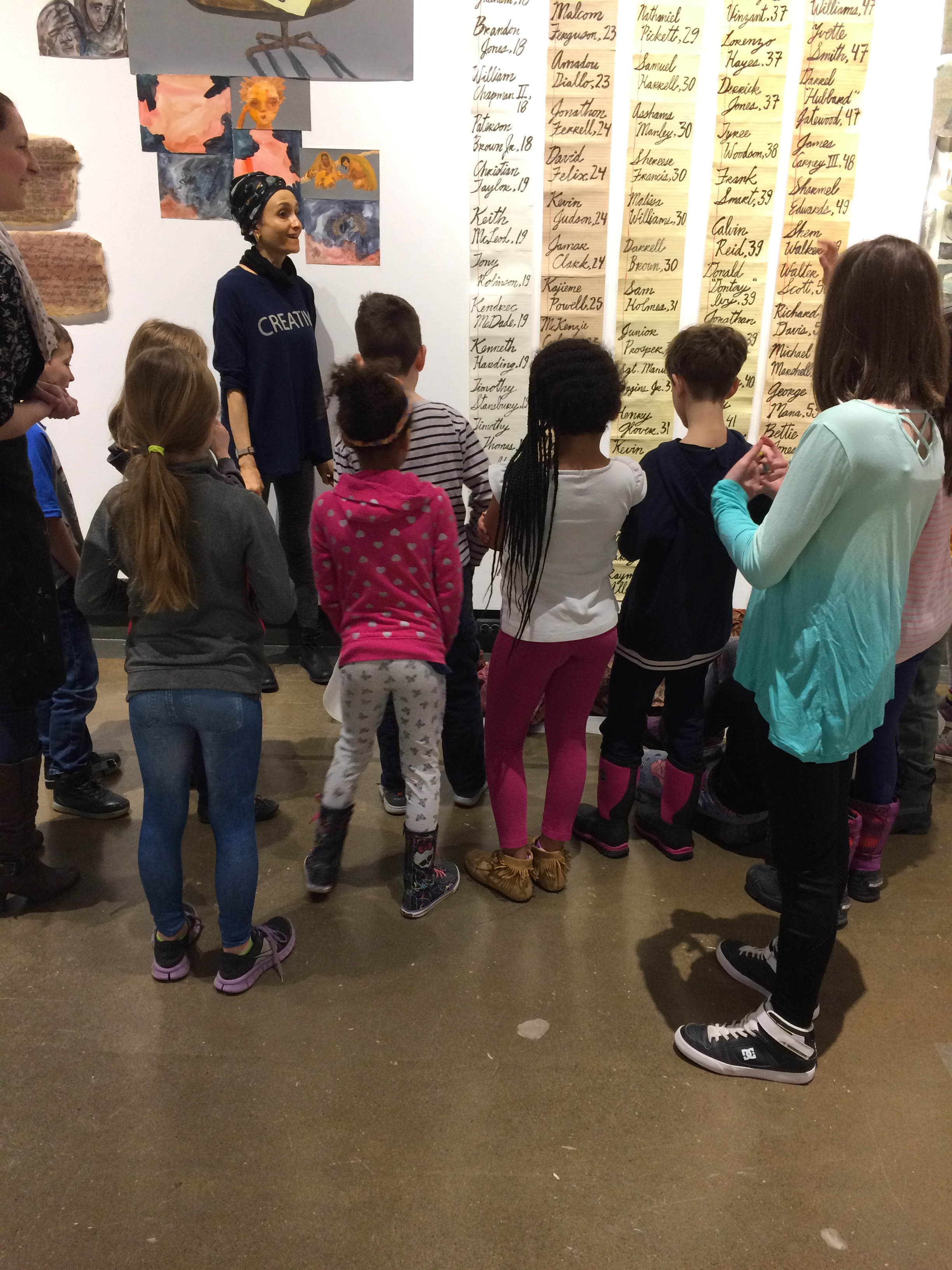 A group of young school children seen from behind listening to artist Lucie Chan explain her exhibition in KWAG's Eastman Gallery