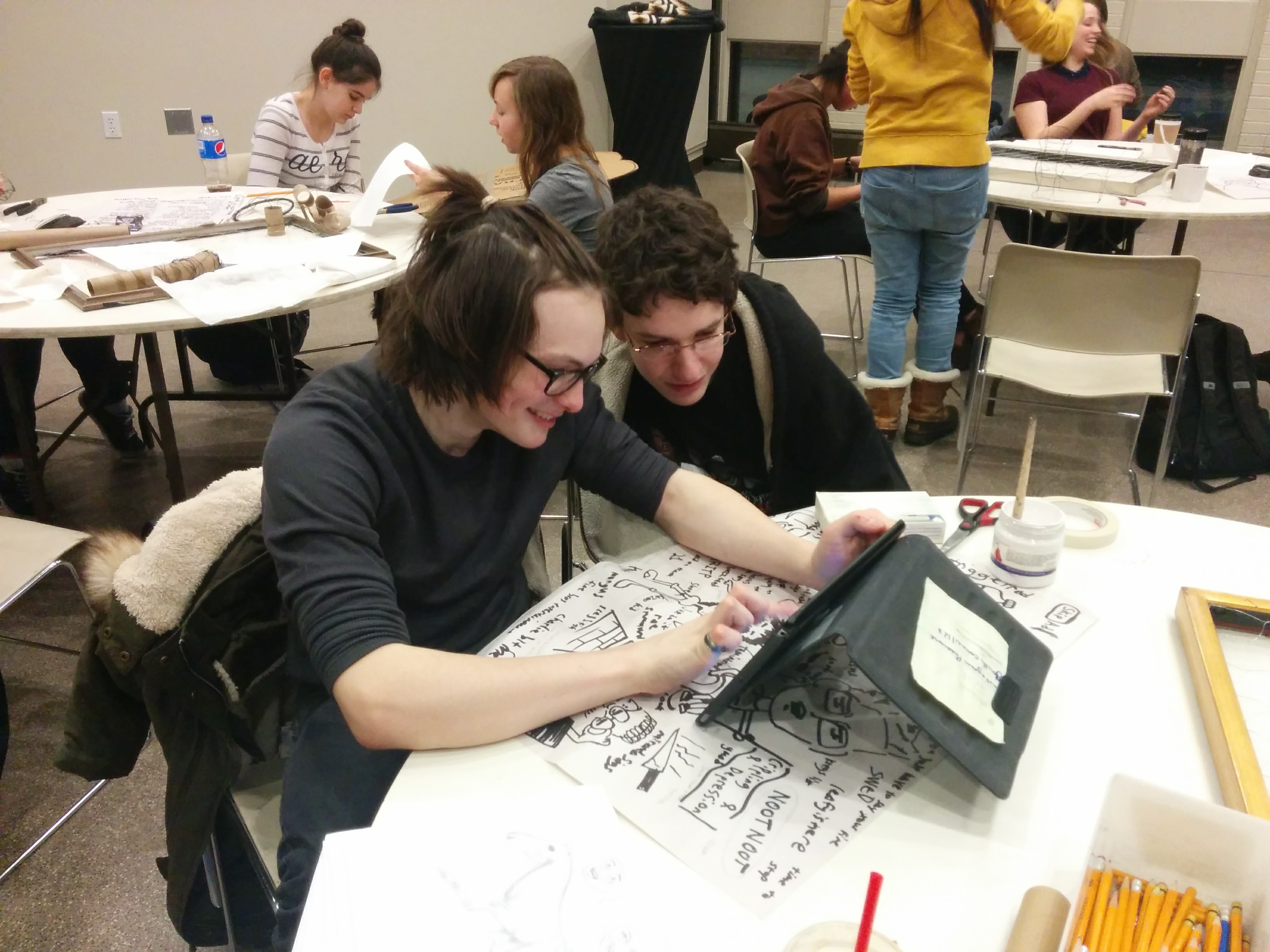 Two teenagers working together on an art project using an iPad at a Youth Council meeting