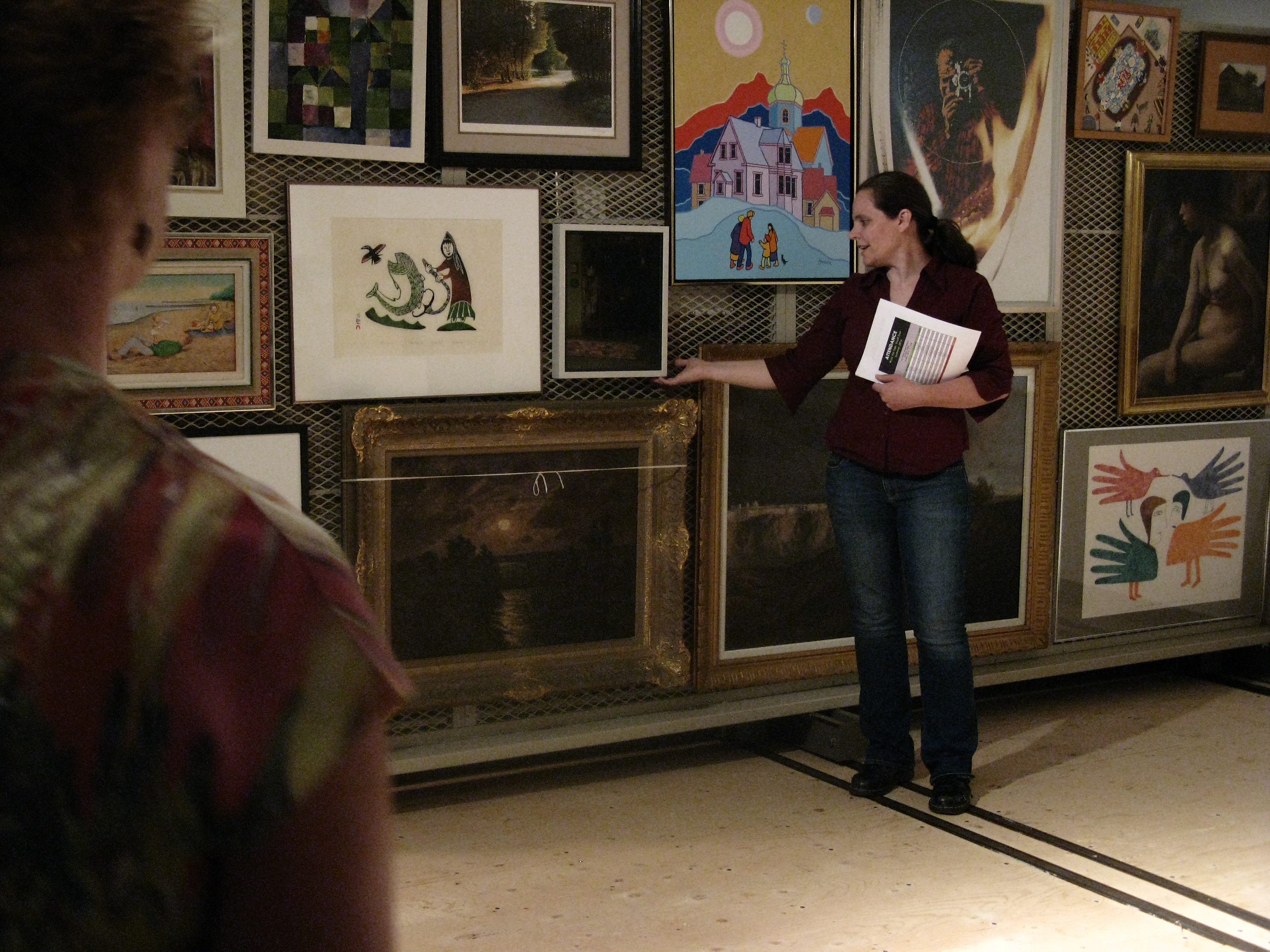 Jennifer Bullock stands before a painting rack in the KWAG vault, gesturing to one of many paintings stored on the rack