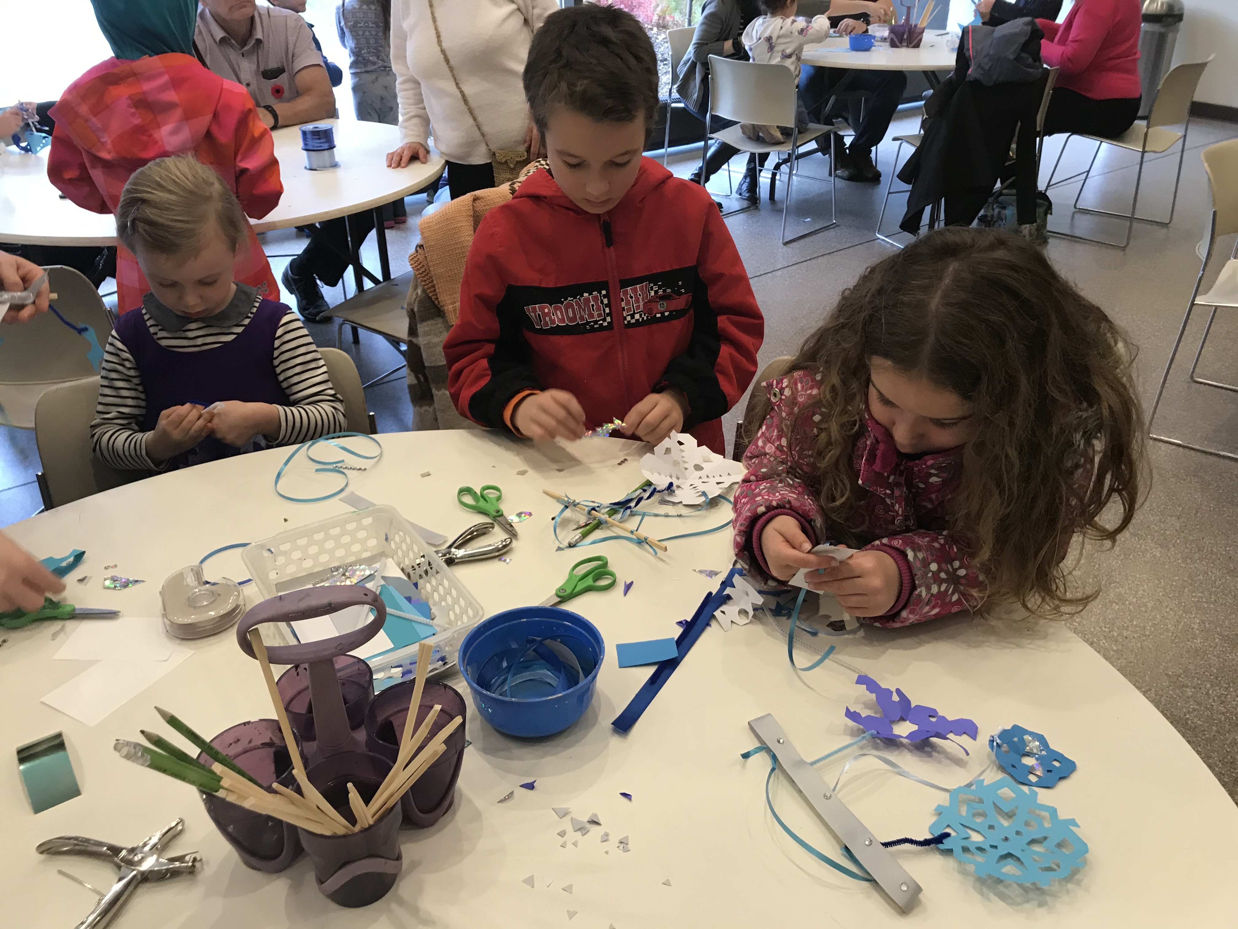 A group of children seated at a table making paper snowflakes