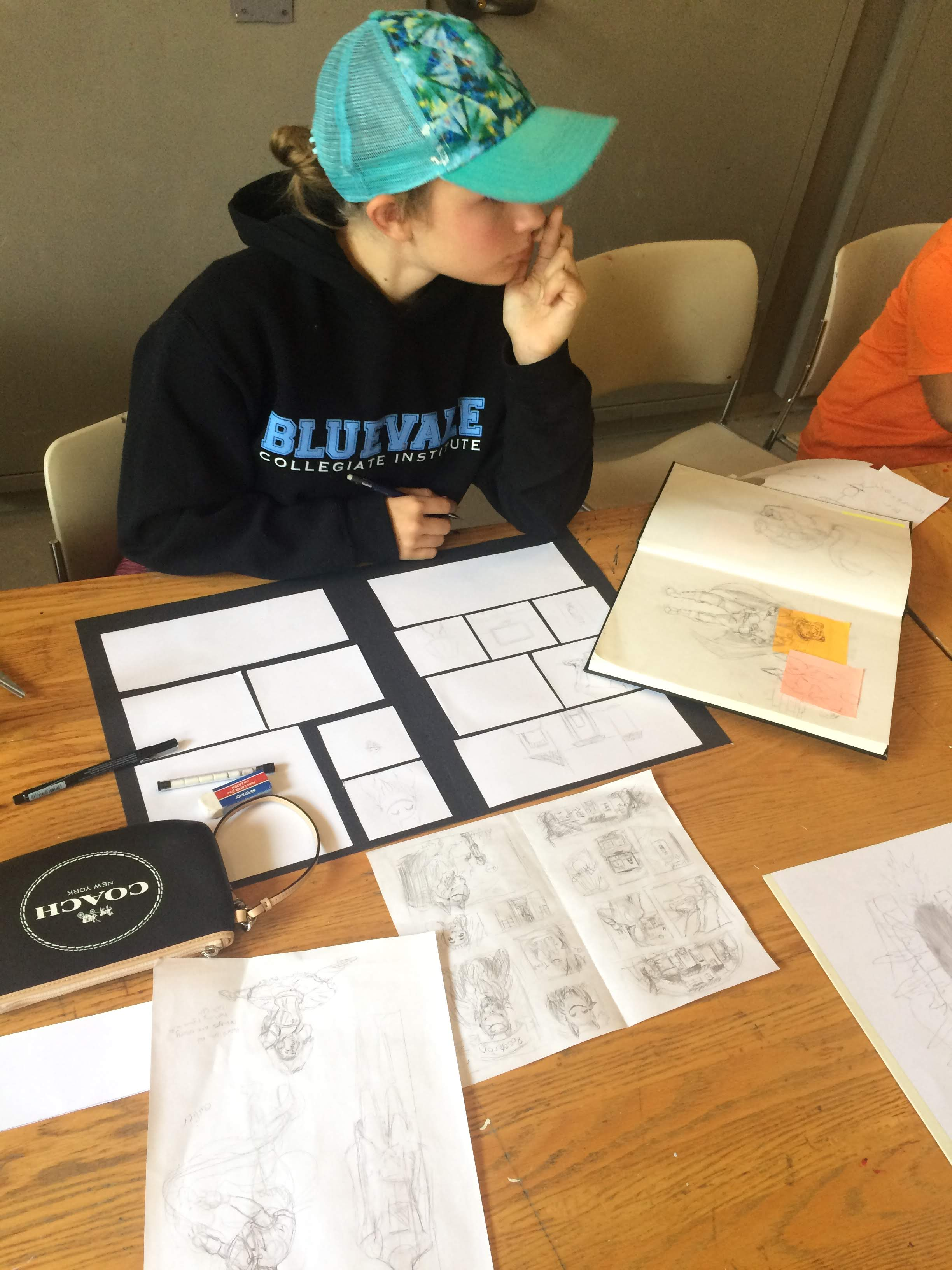 A young girl in a black sweatshirt and teal baseball cap sits at a desk before a series of sketches, notebooks and storyboards