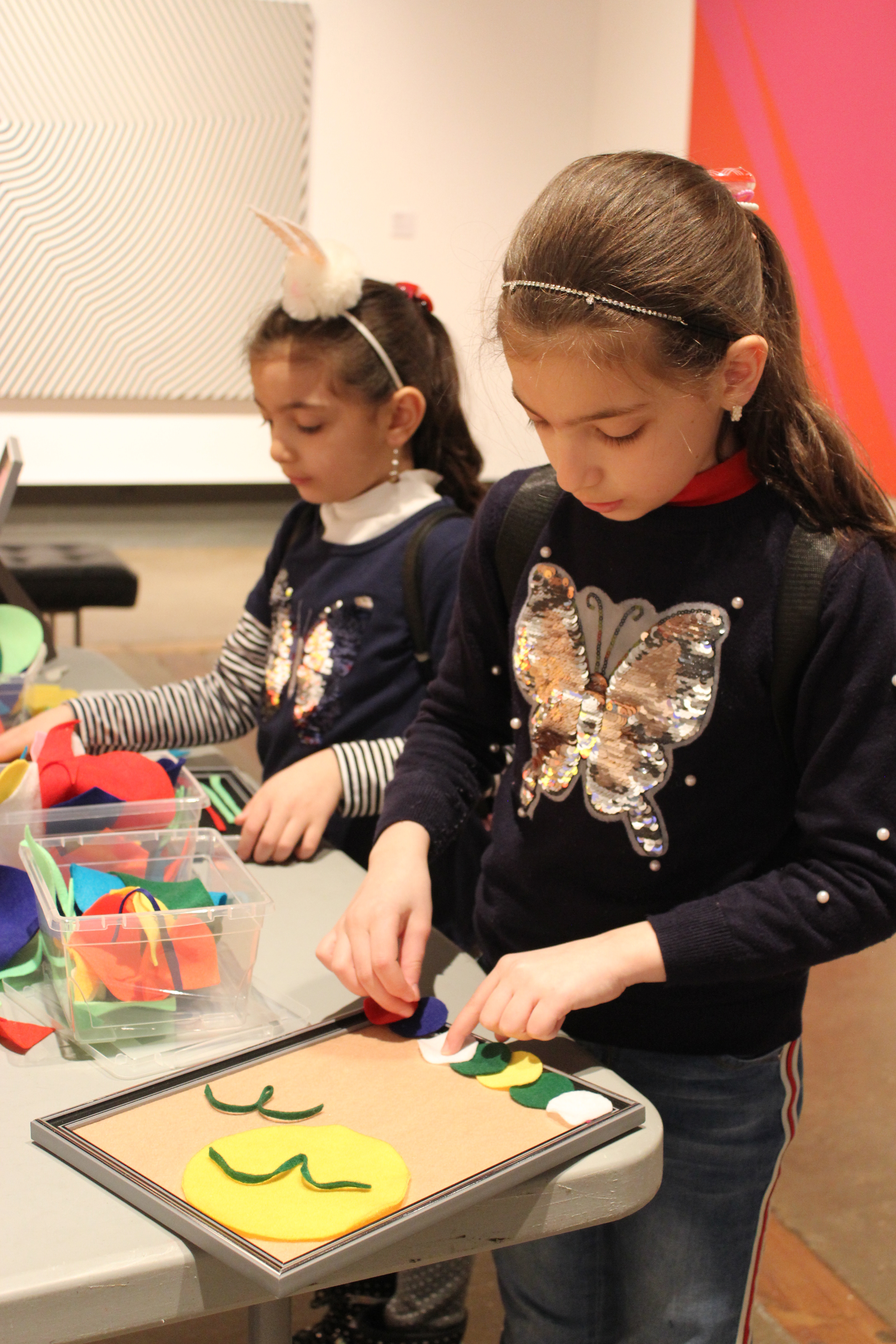 Two young girls making felt collages at a table set up in the gallery with large abstract paintings visible in the background