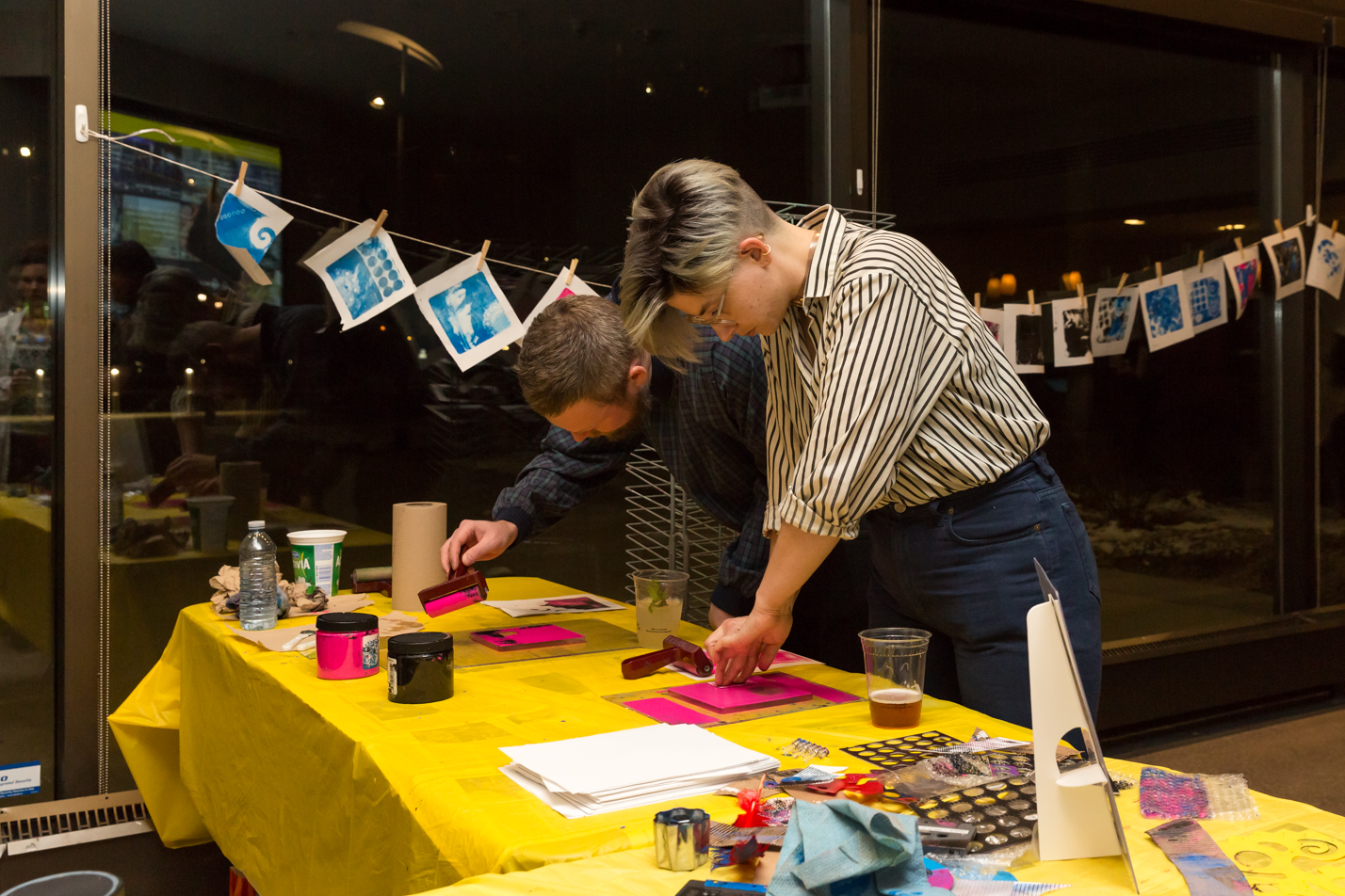 Two young people working on relief prints at a brightly-covered work table covered in printmaking supplies, alongside two cups of beer. A string of finished prints is hanging across a dark reflective window in the background
