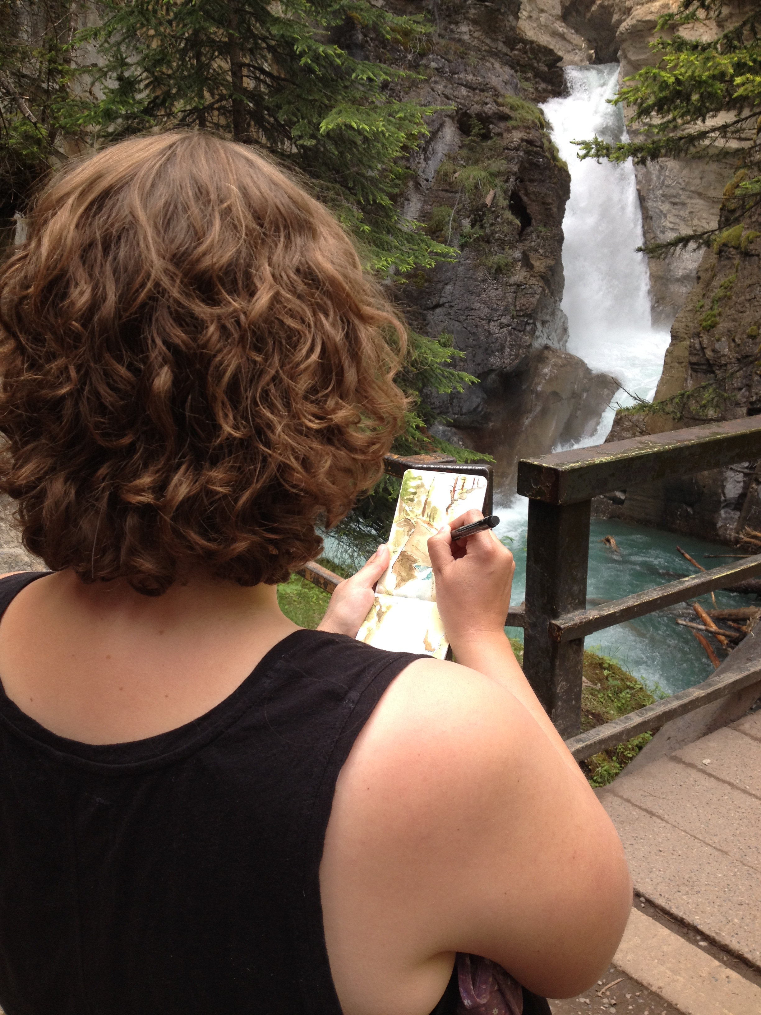 Photo of a woman seen from behind as she sketches while observing a small waterfall on a hiking trail