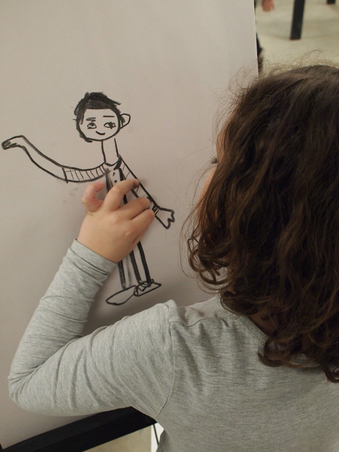 A young girl seen close-up from behind as she draws a simple yet charming figure on a paper pad on an easel