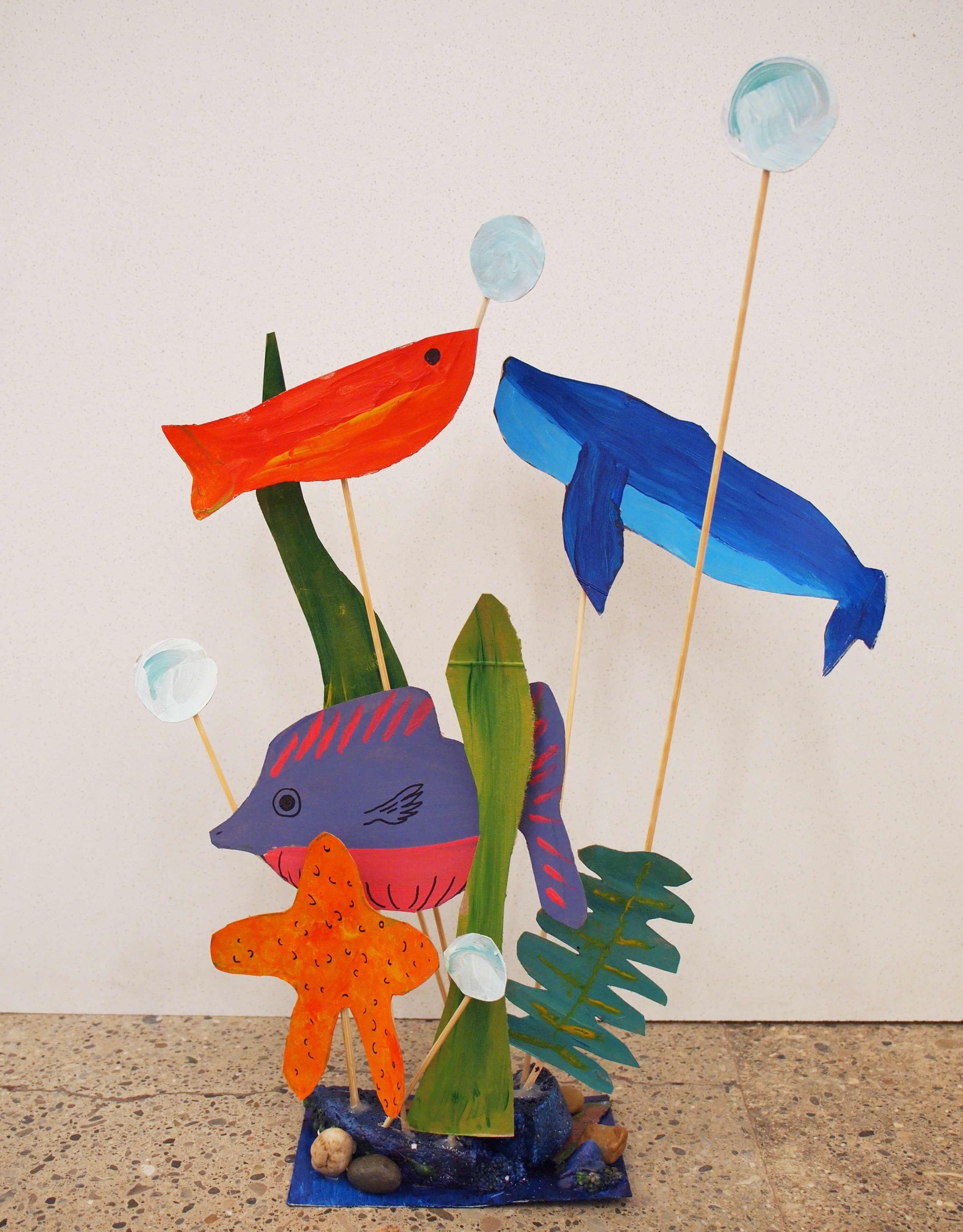 Photo of a painted paper sculpture of fish and whales suspended on wooden skewers