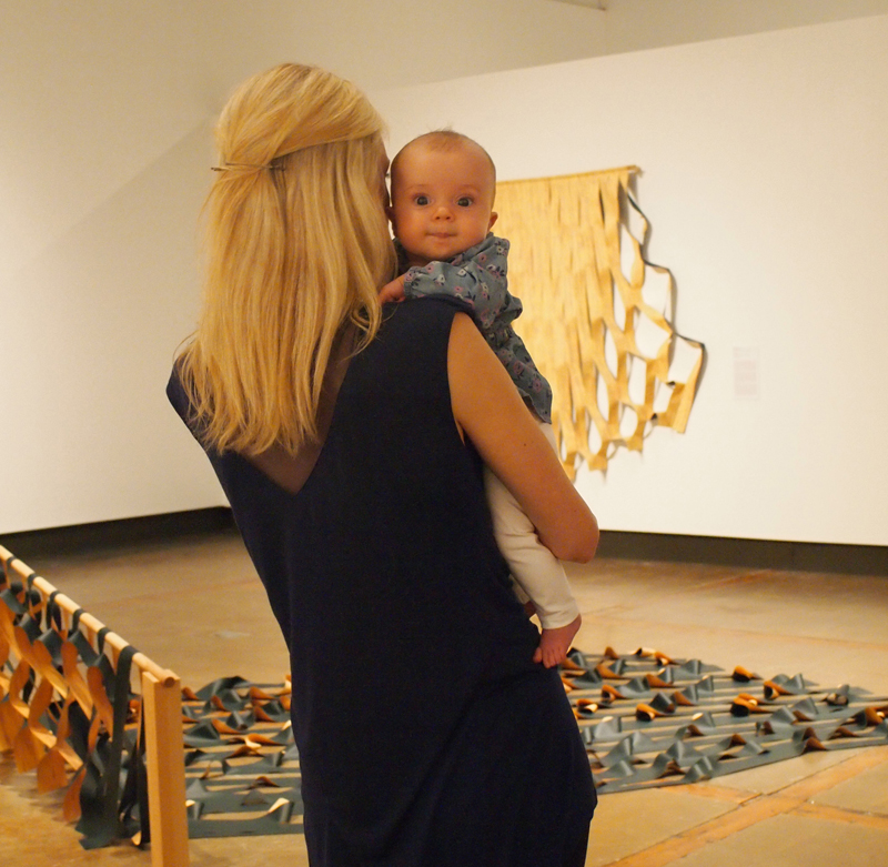 A blonde woman stands with her back to the viewer in the gallery, holding an infant who gazes at the camera from over her shoulder