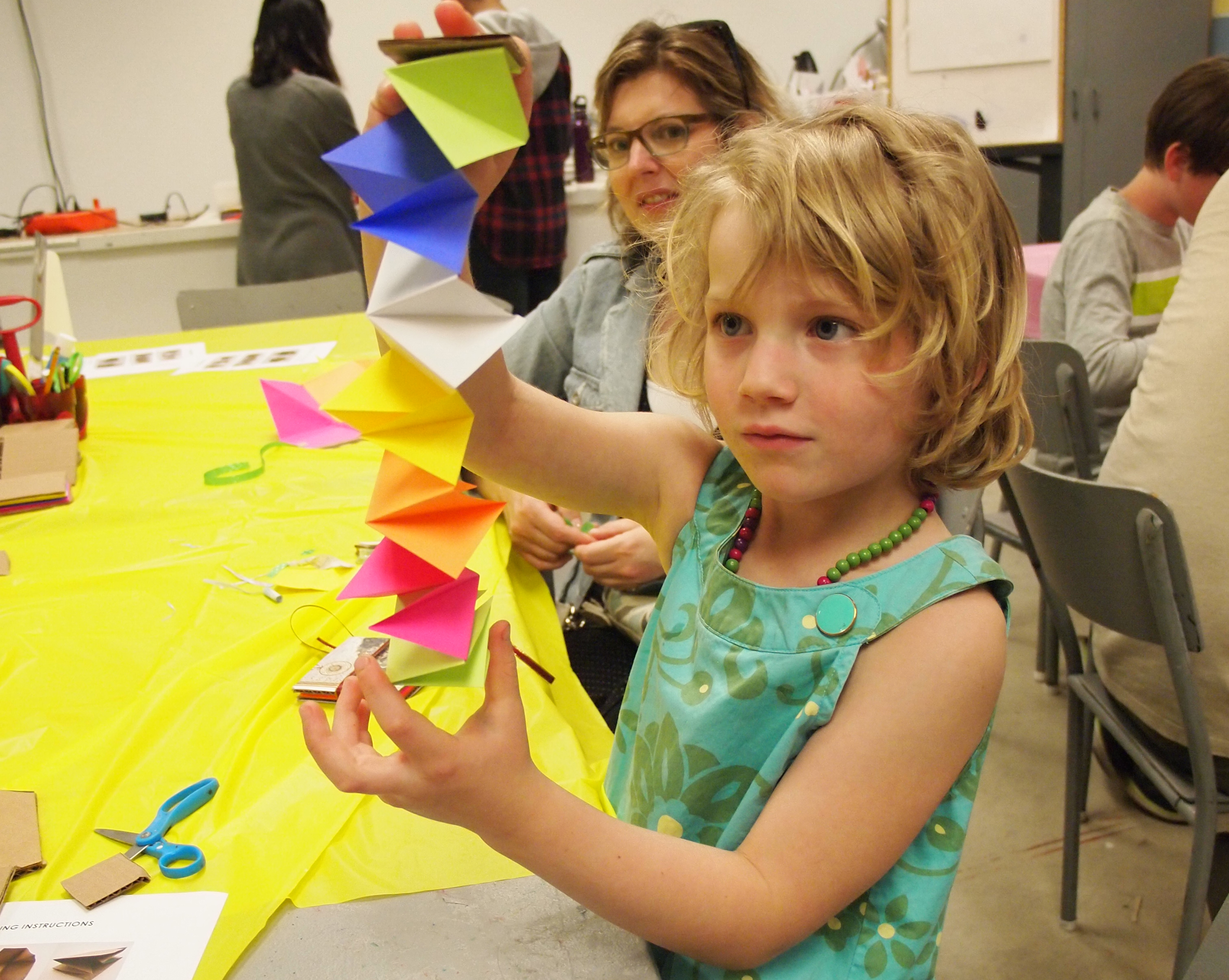 A young girl extends a colourful folded paper sculpture vertically between her hands while her mother looks on in the KWAG studio