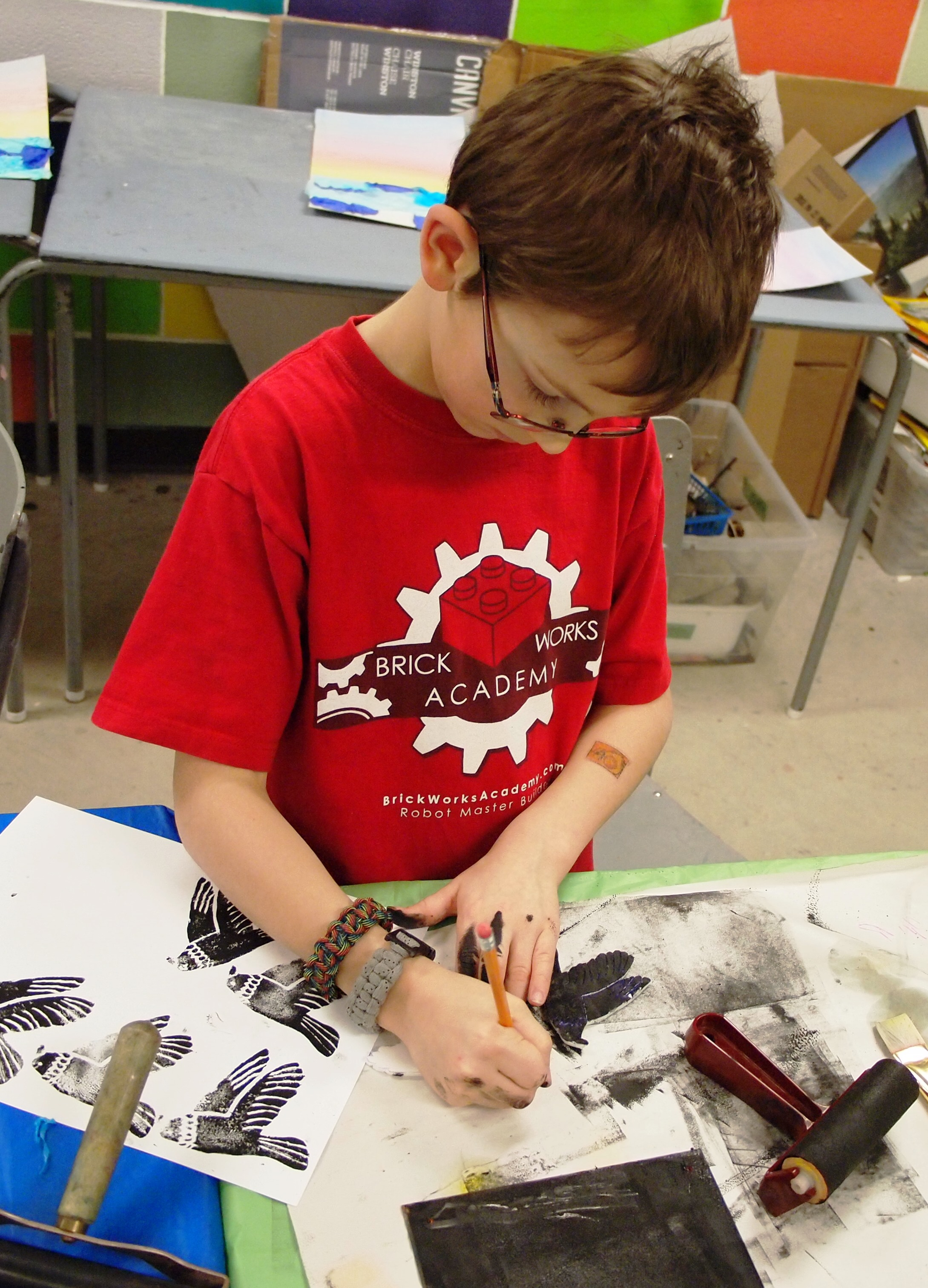 A young boy making multiple bird prints in the KWAG studio