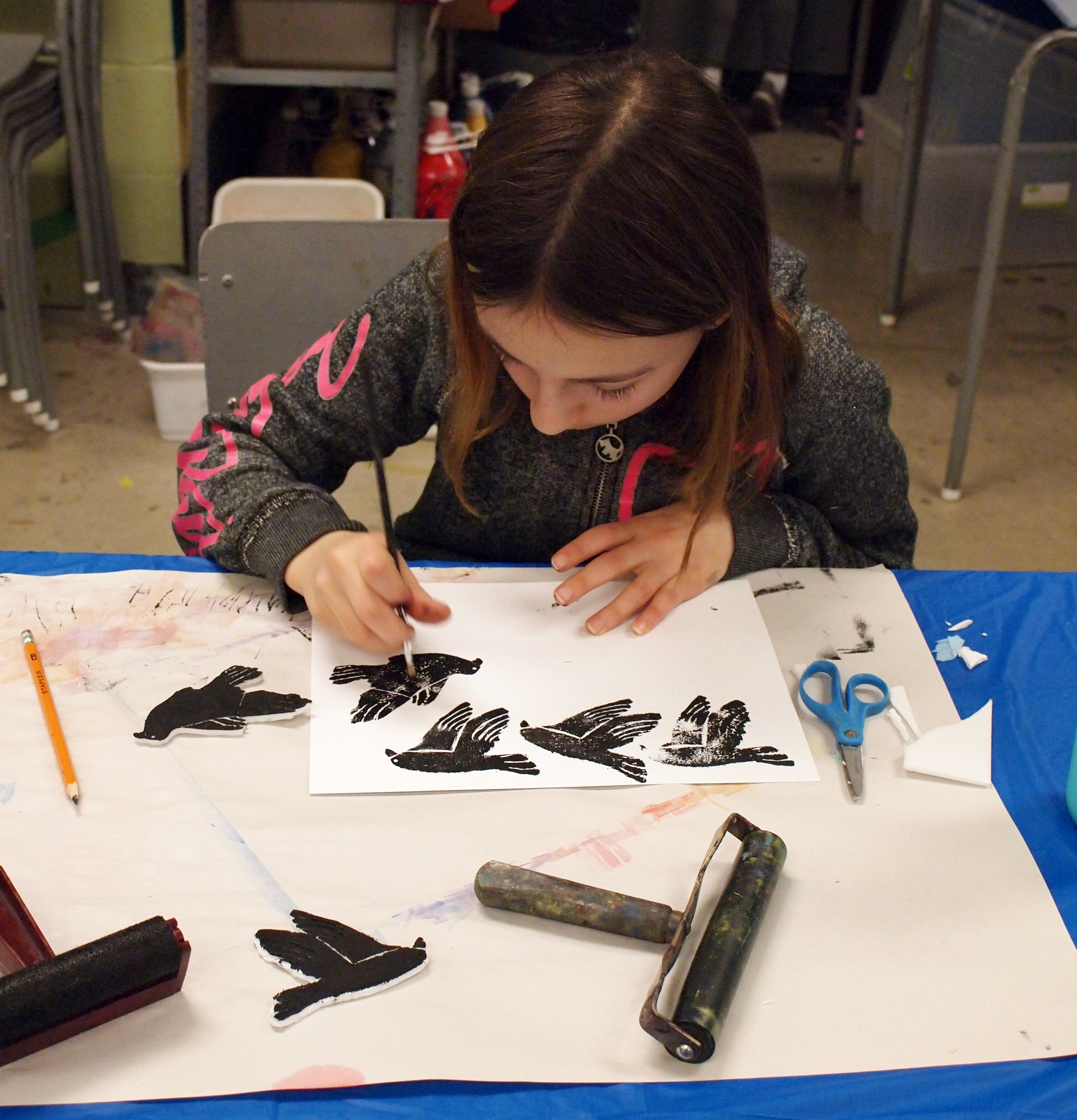 A young girl seated at a studio table touching up a series of black-stamped images of birds with a paintbrush