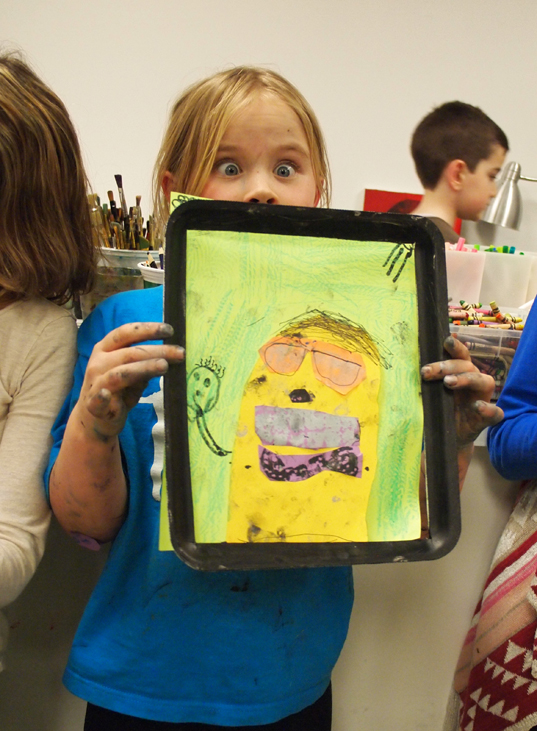 A young girl with comically wide eyes holds up an abstract portrait painting over the lower half of her face