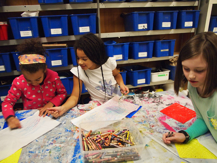 Three young girls sharing a table and crayons while creating texture rubbing drawings