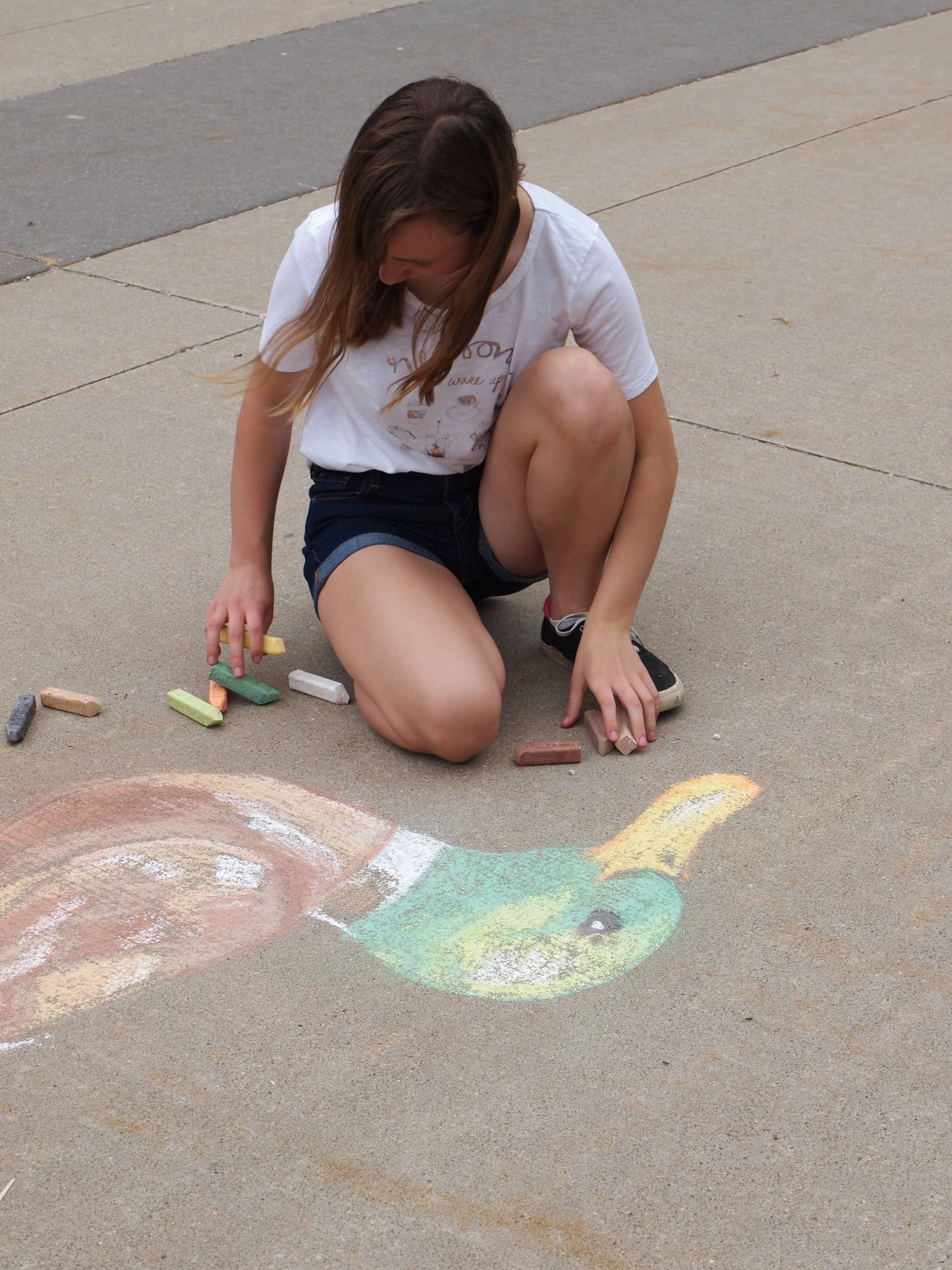 A young girl kneels on concrete alongside a chalk drawing of a duck; pieces of chalk sit on the ground close at hand