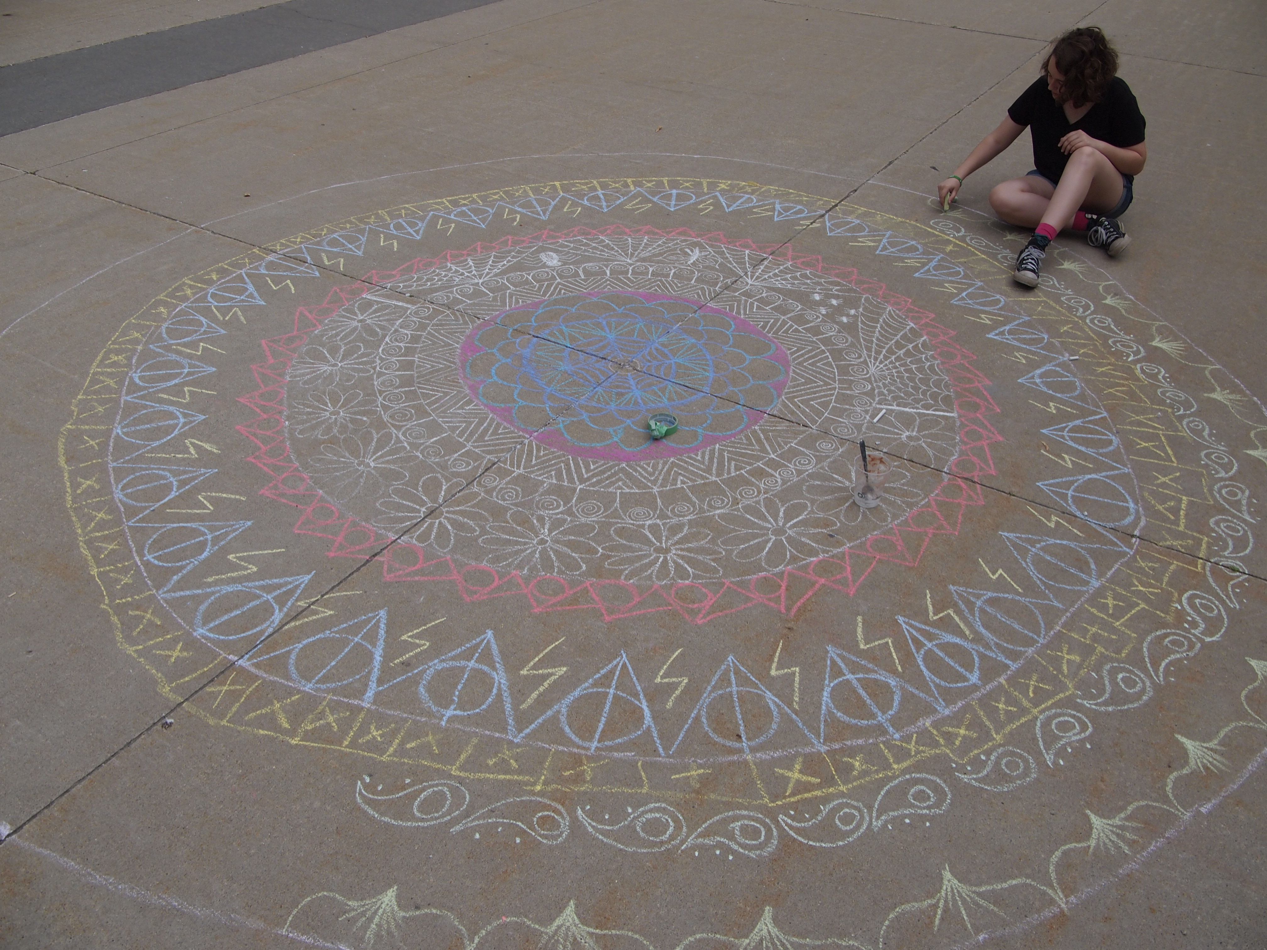 Overhead photo of a young girl drawing a large chalk mandala on the concrete outside Centre In The Square