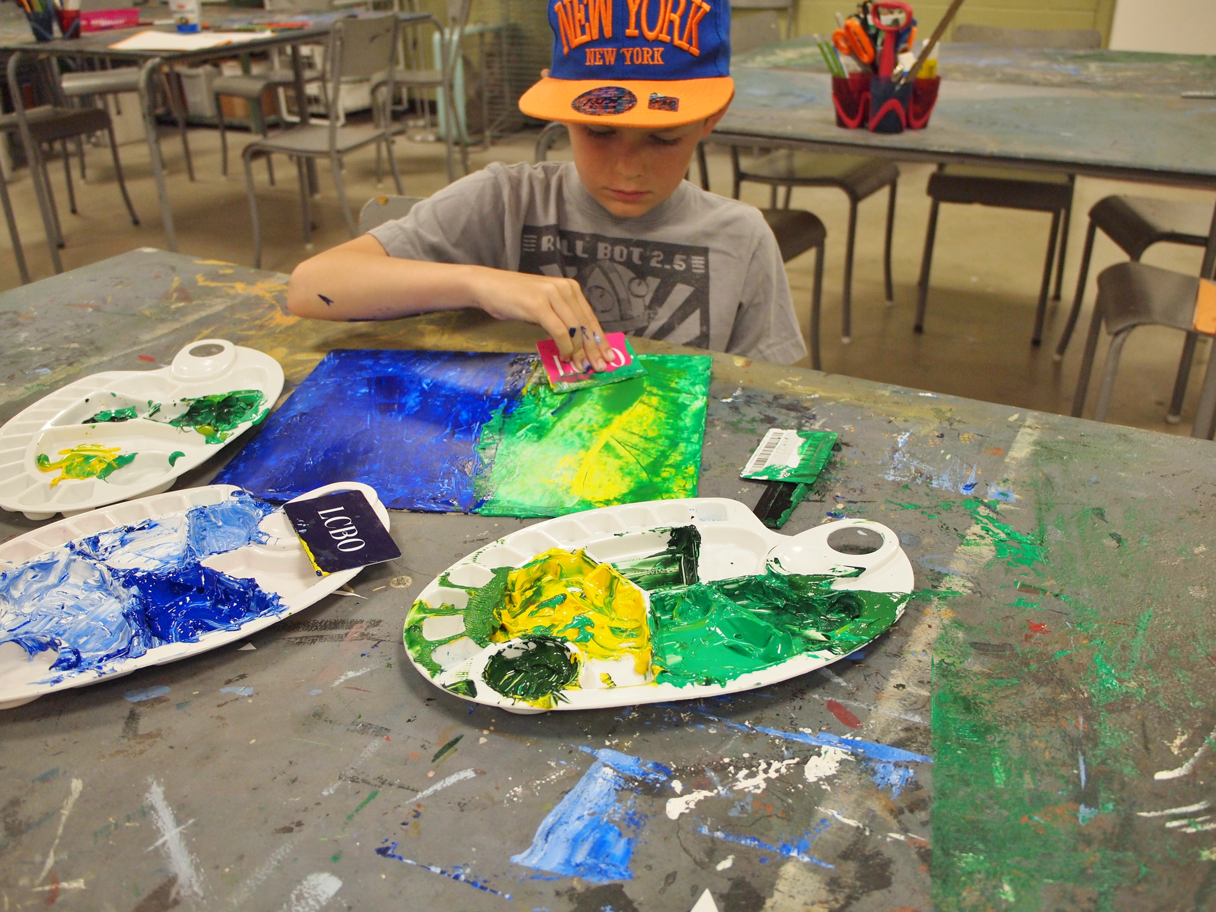 Photo of a young boy in grey shirt and baseball hat using a plastic card to scrape layers of bright colours on a simple landscape of grass and sky, with three messy paint palettes spread out on the table in front of him